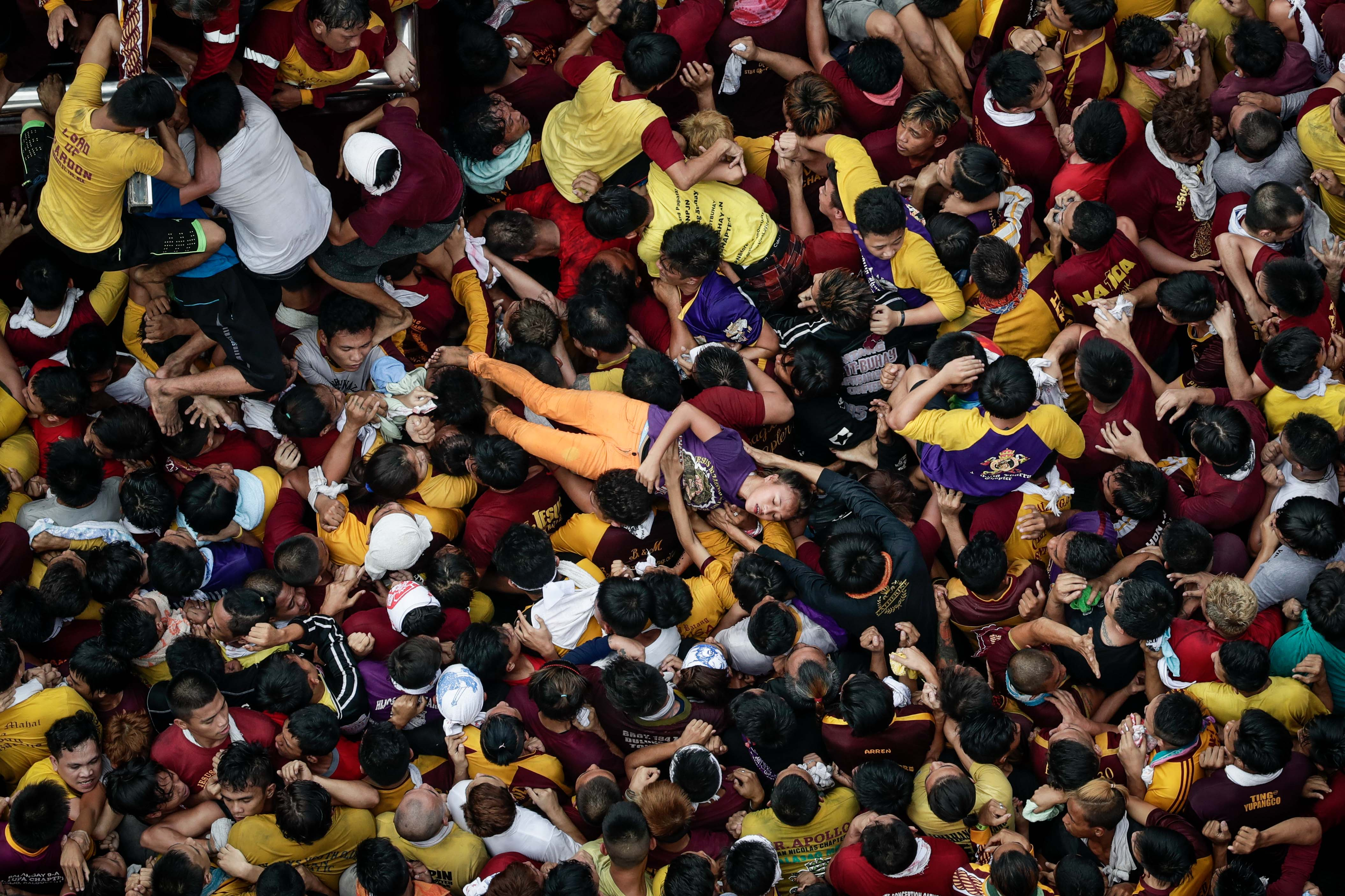 A woman is carried off by a crowd of devotees near the statue of the Black Nazarene during the procession at the Jones Bridge in Manila on Jan. 9, 2017
