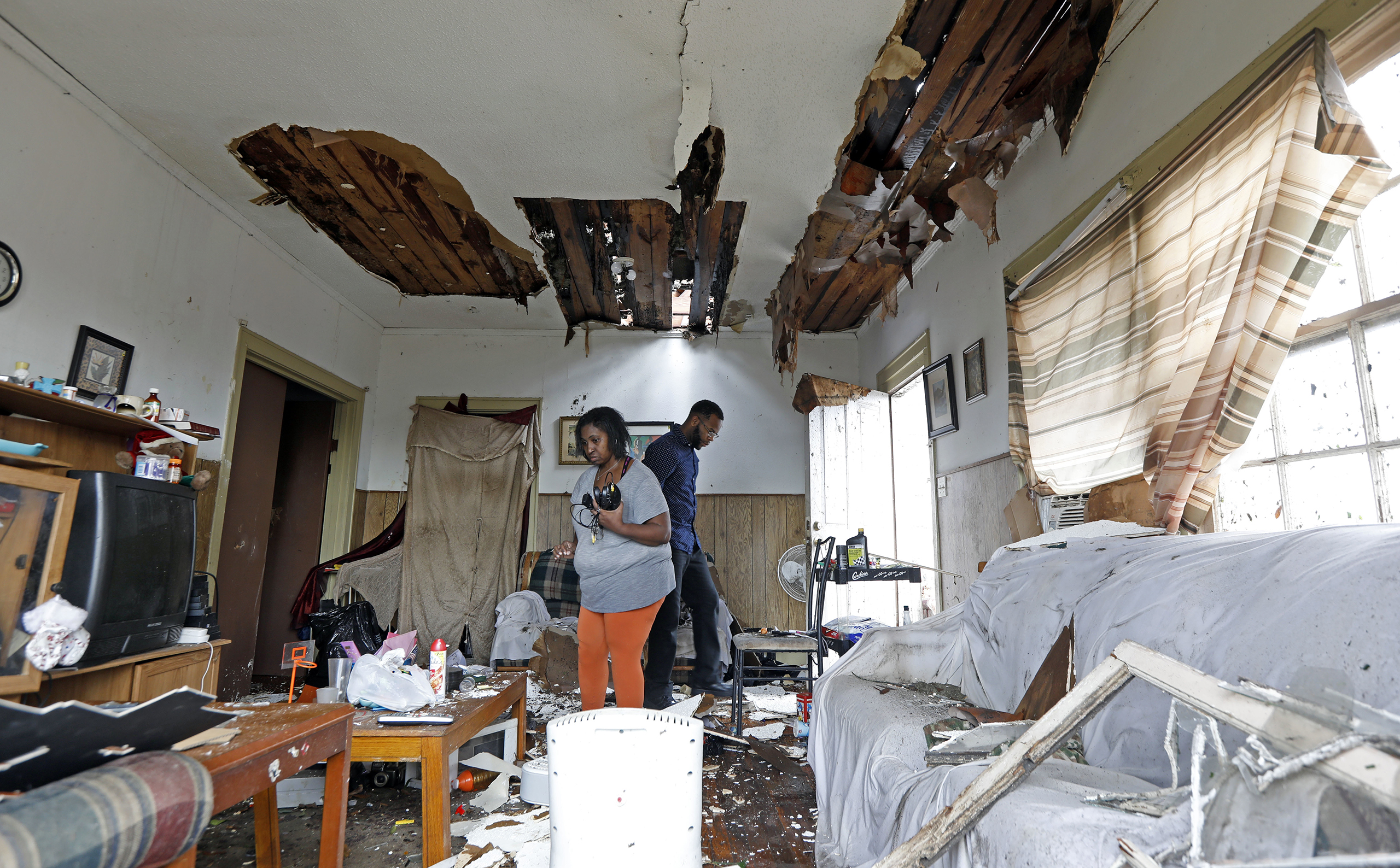 Donna Thompson, and a friend, salvage some of her possessions on Jan. 21, 2017, after a morning tornado ripped her roof off in Hattiesburg, Miss.