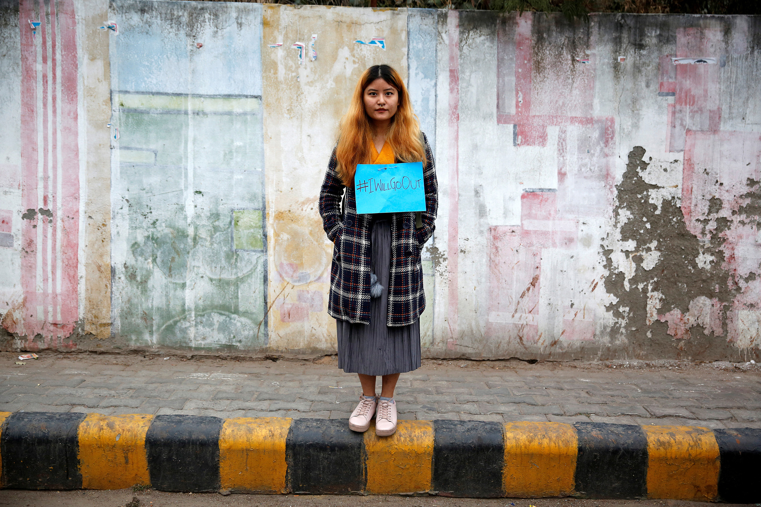 A woman waits for the start of the #IWillGoOut rally, organized to show solidarity with the Women's March in Washington, along a street in New Delhi, India Jan.21, 2017.