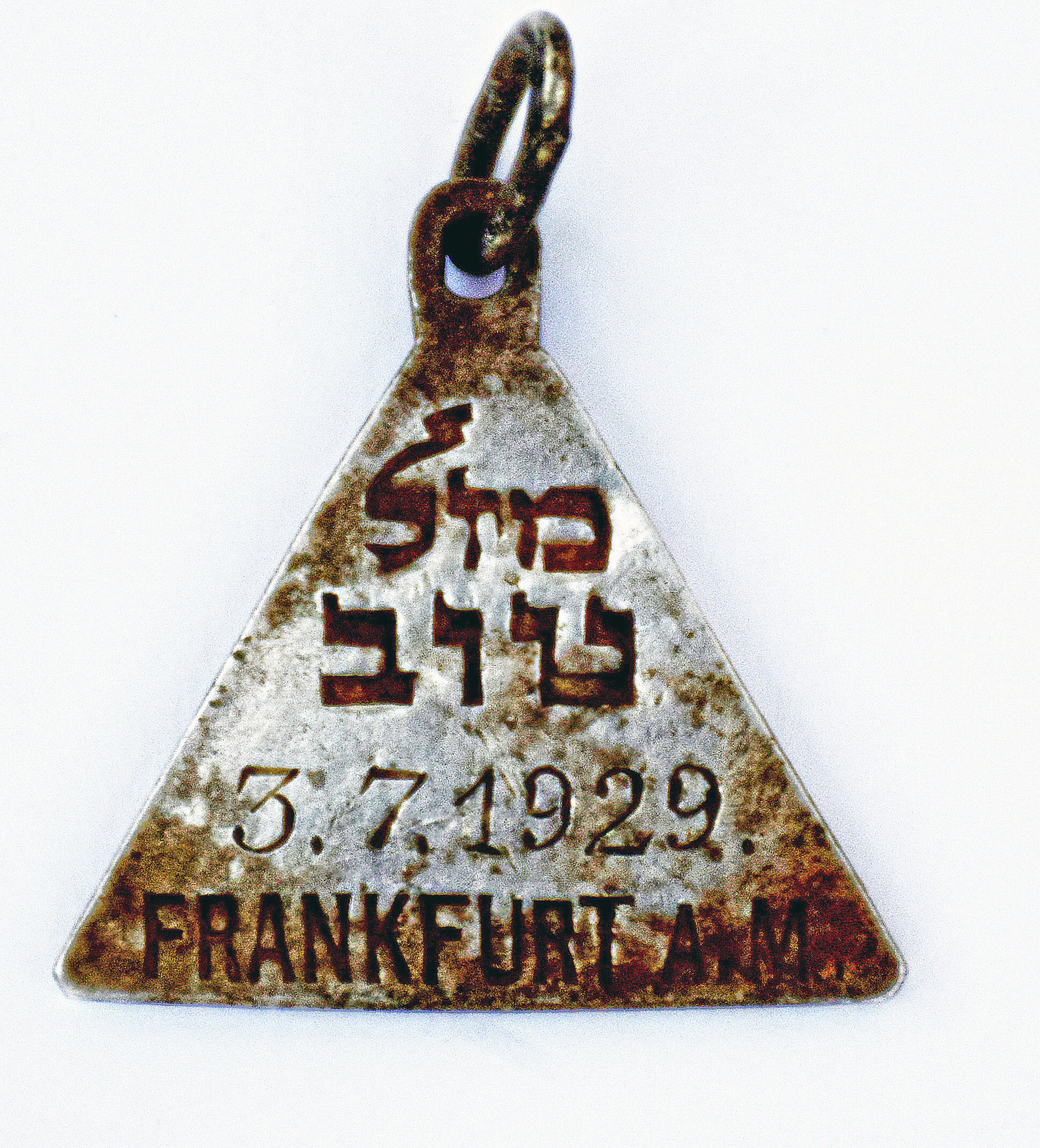 This undated photograph released by the Israel Antiquities Authority shows a pendant that appears identical to one belonging to Anne Frank, Israel's Yad Vashem Holocaust memorial said Sunday. Yad Vashem says it has ascertained the pendant belonged to Karoline Cohn _ a Jewish girl who perished at Sobibor and may have been connected to the famous diarist. Both were born in Frankfurt in 1929 and historians have found no other pendants like theirs. The triangular piece found has the words  Mazal Tov  written in Hebrew on one side along with Cohn's date of birth and the Hebrew letter  heh,  an initial for God, as well as three Stars of David on the other.