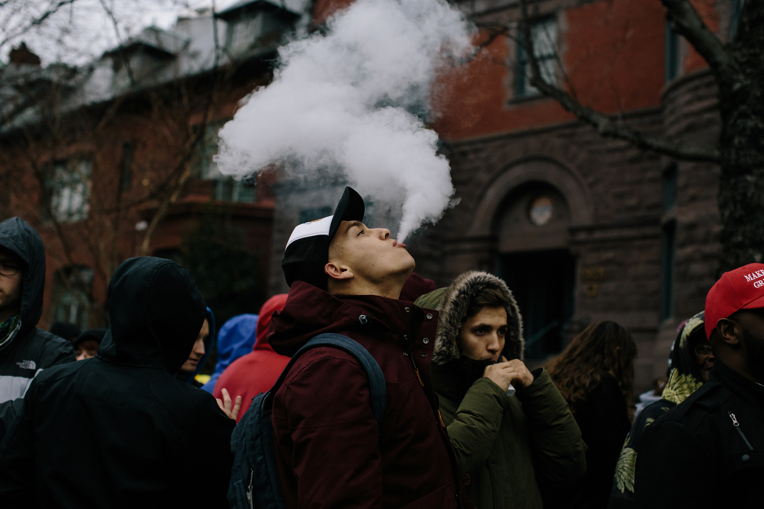Dmytro Karaban, 21, from New York City, blows vape smoke while waiting in line for a free joint Friday during the #Trump420 event in Washington on Jan. 20, 2017.