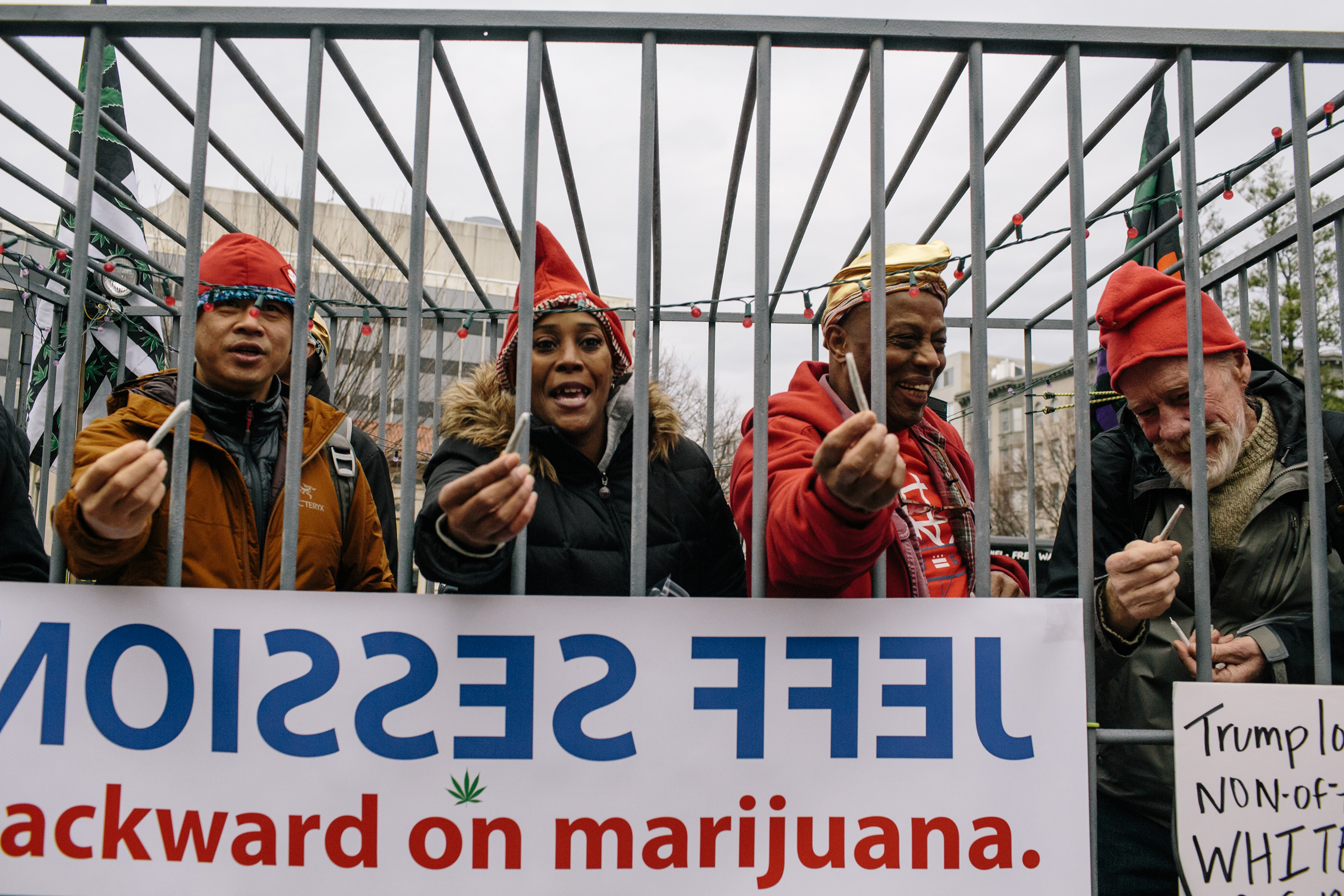 Kevin Keefe, right, and other volunteers stand in a pretend jail to pass out joints for DCMJ, a D.C.-based marijuana advocacy group, during the #Trump420 event on Jan. 20, 2017 in Washington.