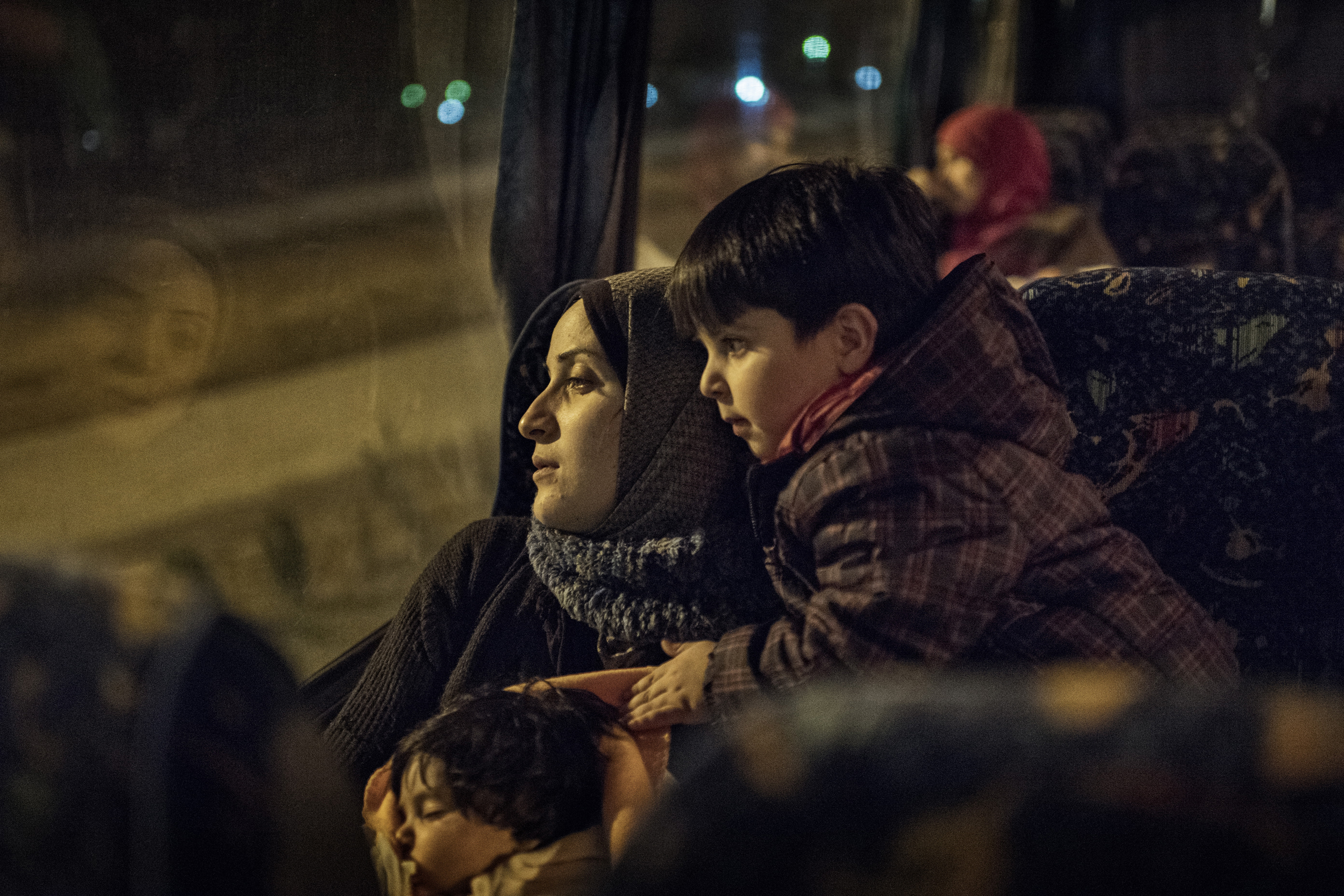 Taimaa Abazli, a Syrian refugee, with her baby Heln and son Wael, take an overnight bus to Athens, where they will learn which country will grant them asylum, Jan. 19, 2017.