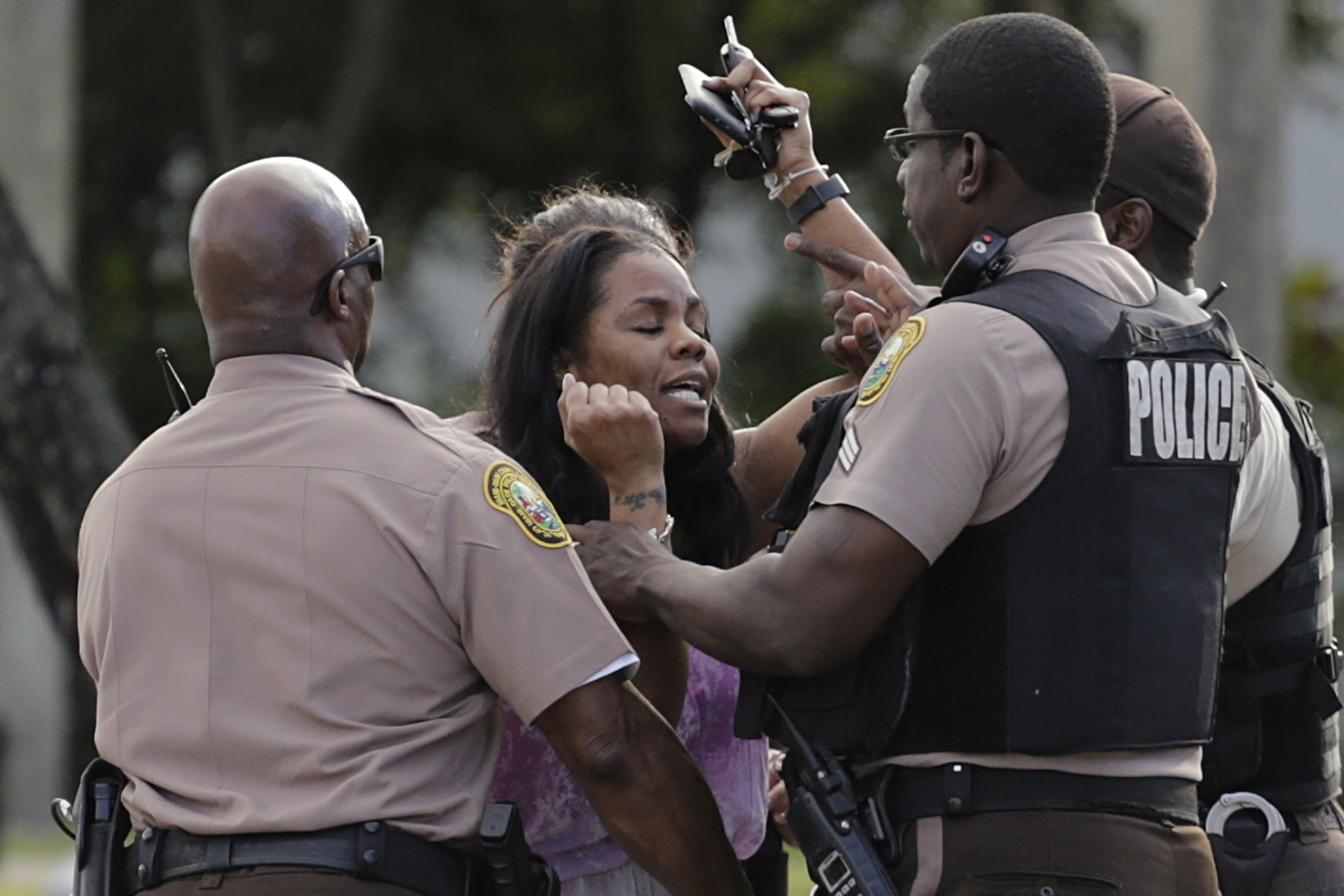 A concerned mother is met by Miami-Dade police officers as she searches for her child after several were injured in a shooting at Martin Luther King Jr. Memorial Park in Miami-Dade, Fla., on, Jan. 16, 2017.