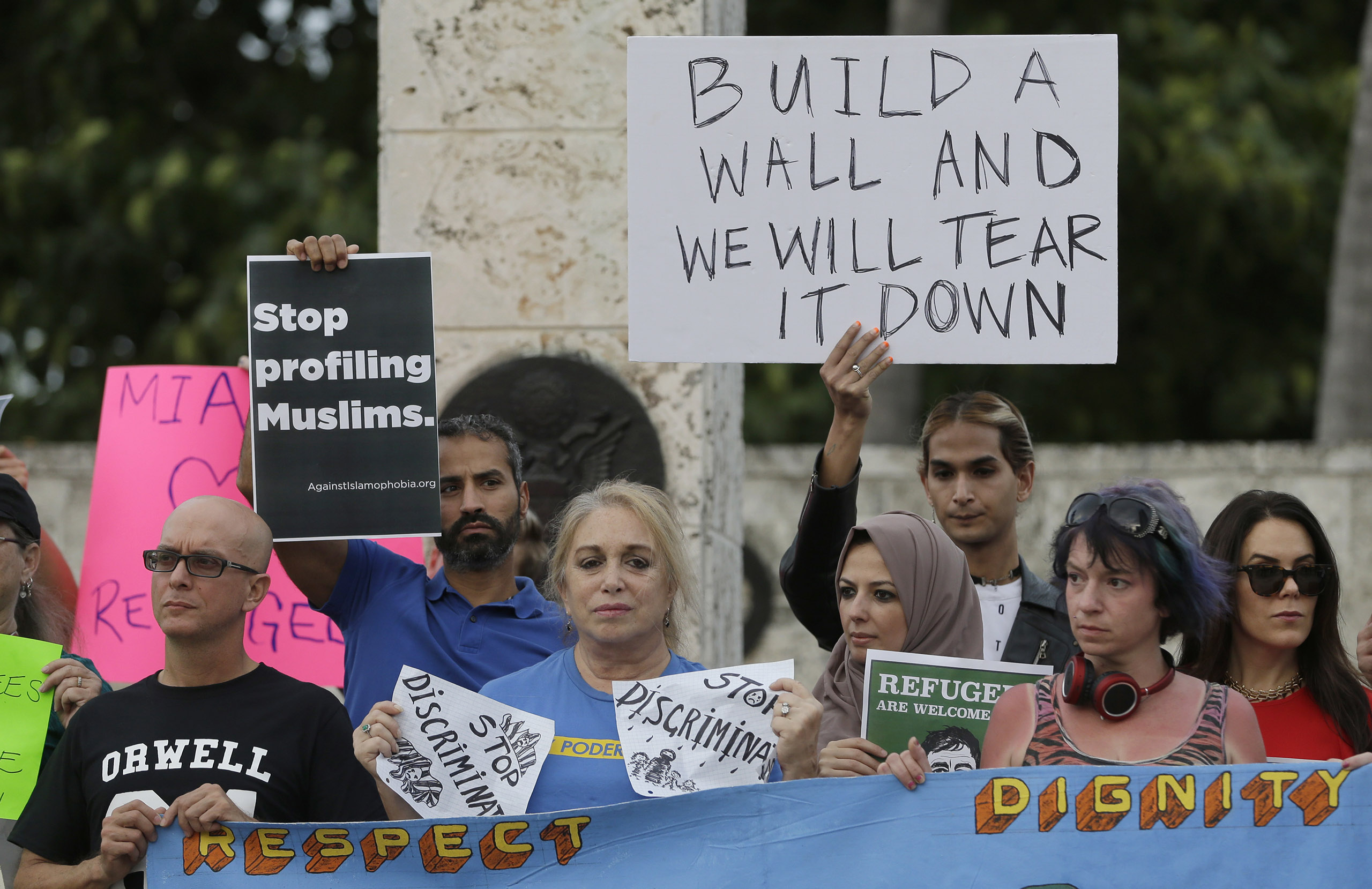 Protesters hold signs during a rally against President Donald Trump's executive order on immigration in downtown Miami. on Jan. 26, 2017.