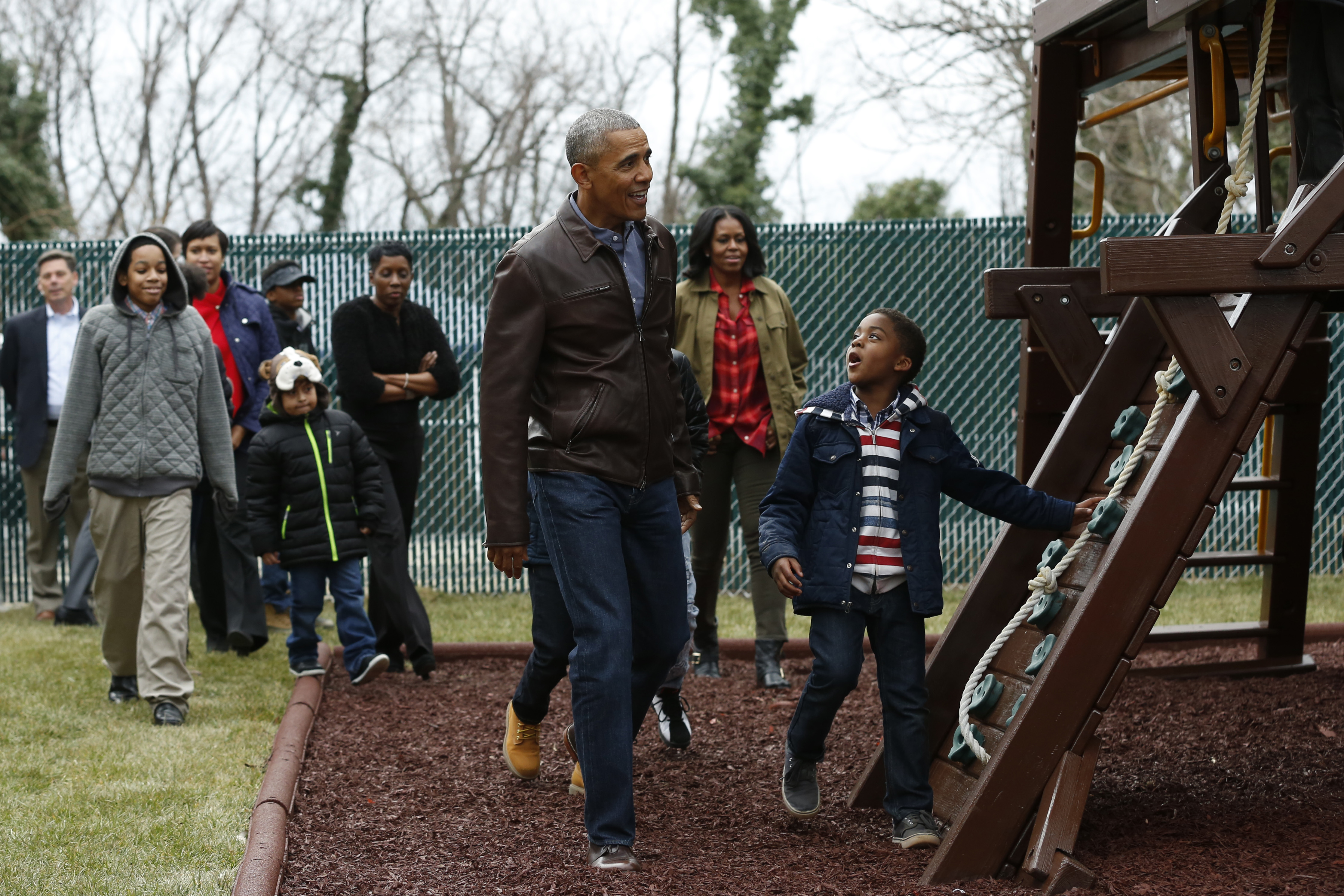US President Barack Obama and First Lady Michelle Obama play with children on a swing donated by the first family at the Jobs Have Priority Shelter in Washington, DC on January 16, 2017. / AFP / YURI GRIPAS (Photo credit should read YURI GRIPAS/AFP/Getty Images)