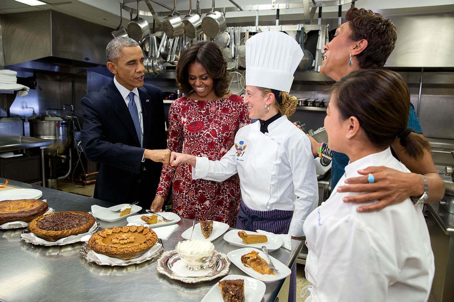 President Barack Obama fist bumps Executive Pastry Chef Susie Morrison after sampling pies with First Lady Michelle Obama, ABC News Anchor Robin Roberts and Executive Chef Cris Comerford during an interview about Thanksgiving in the White House Kitchen, Nov. 19, 2014.