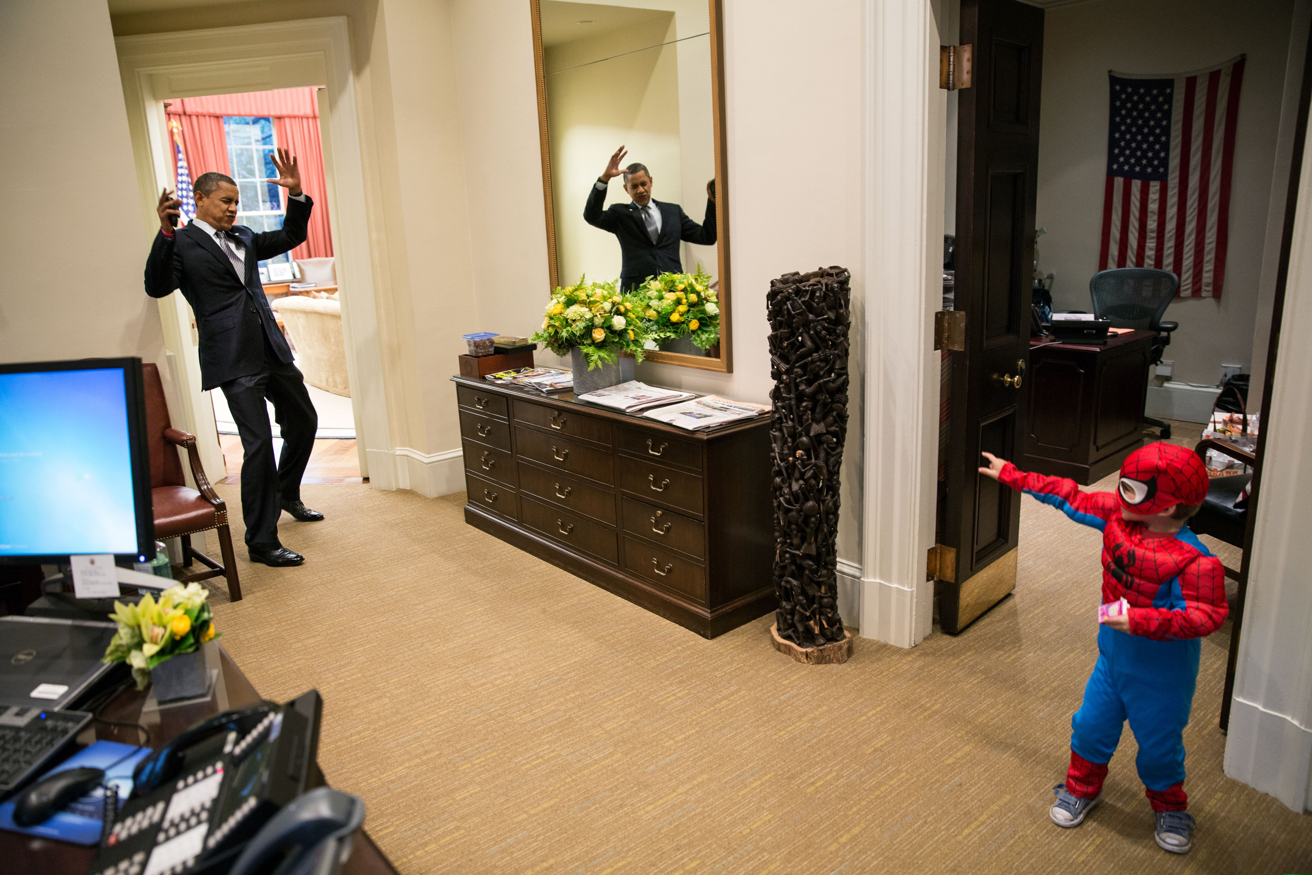 Obama pretends to be caught in Spider-Man's web as he greets Nicholas Tamarin, 3, just outside the Oval Office on Oct. 26, 2012.