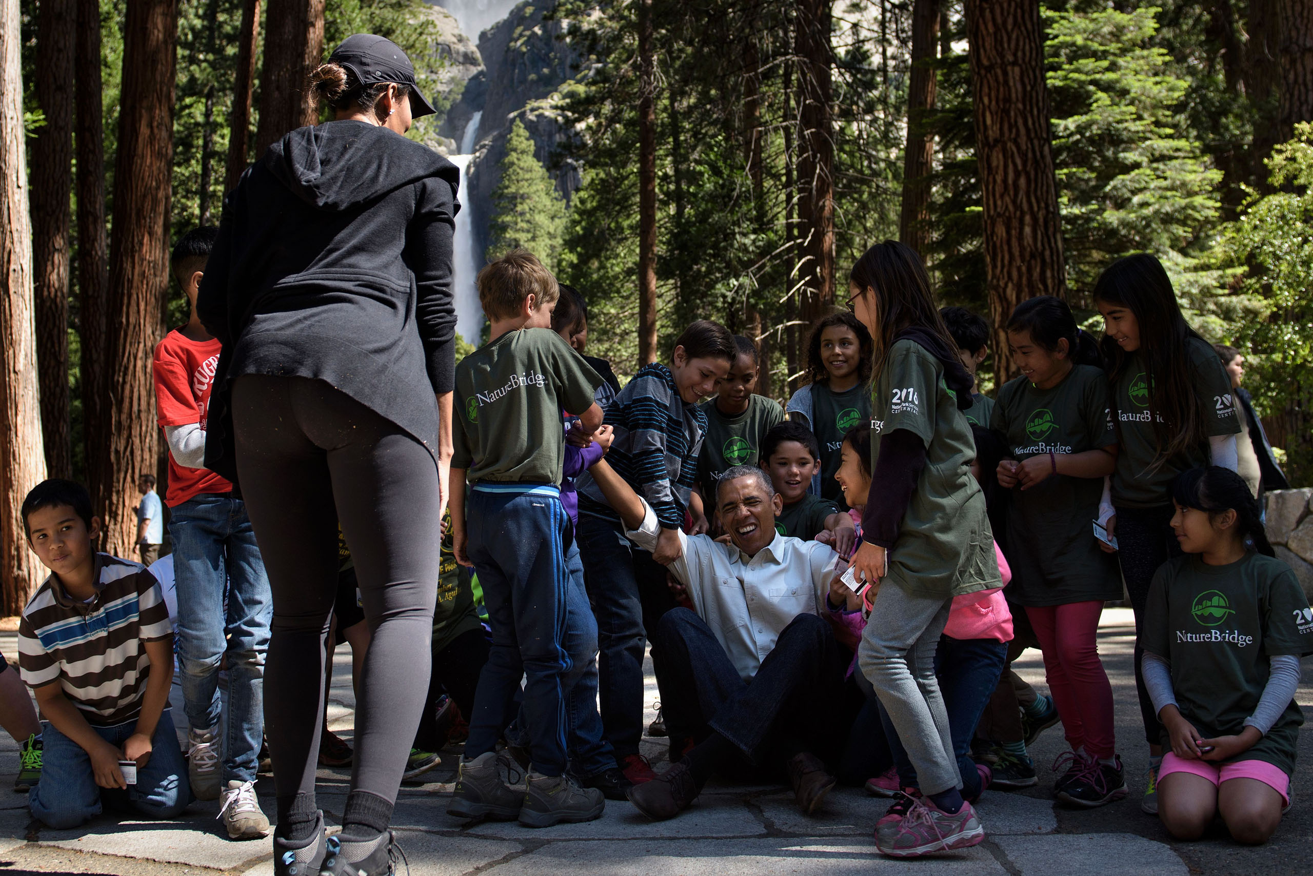 Children help Obama stand after he spoke to them about the  Every Kid in the Park  initiative in Yosemite National Park, California while celebrating the 100th year of US National Parks, on June 18, 2016.