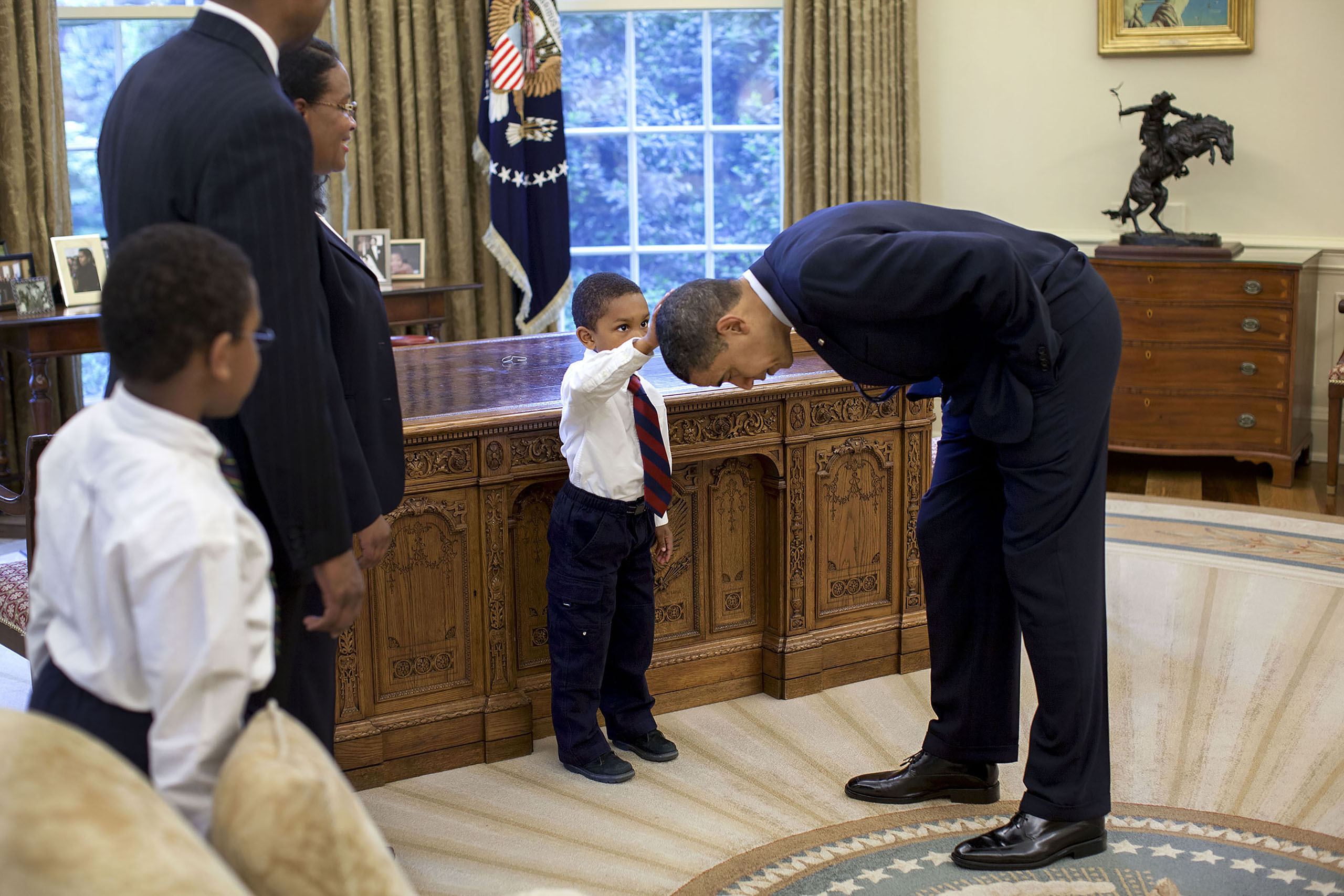 Obama bends over so Jacob Philadelphia, the son of a National Security staff member, can pat his head during a family visit to the Oval Office on May 8, 2009.