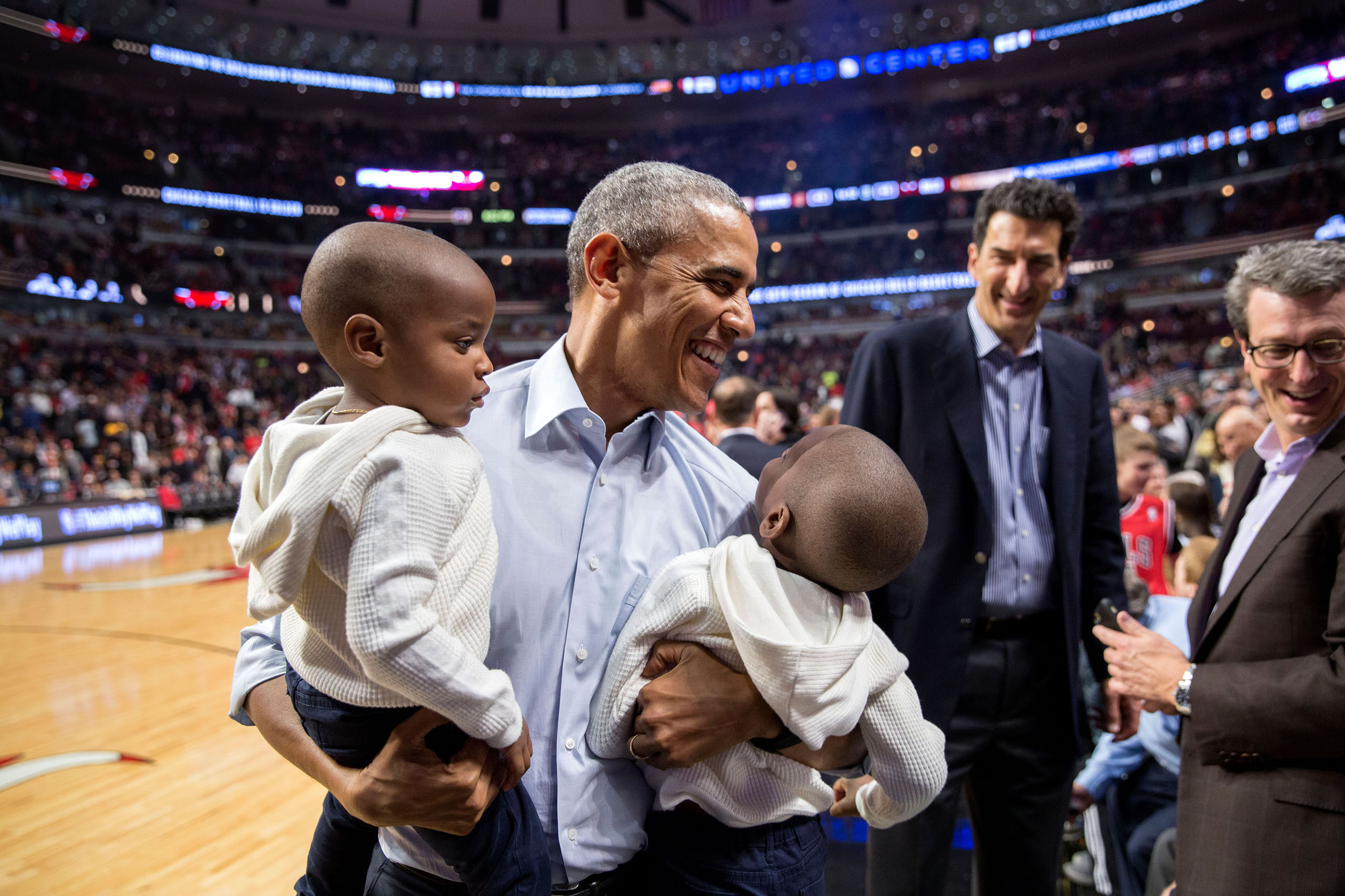 Obama holds two youngsters while posing for a photo with them during halftime of the Chicago Bulls-Cleveland Cavaliers basketball game at the United Center in Chicago, Ill., on Oct. 27, 2015.