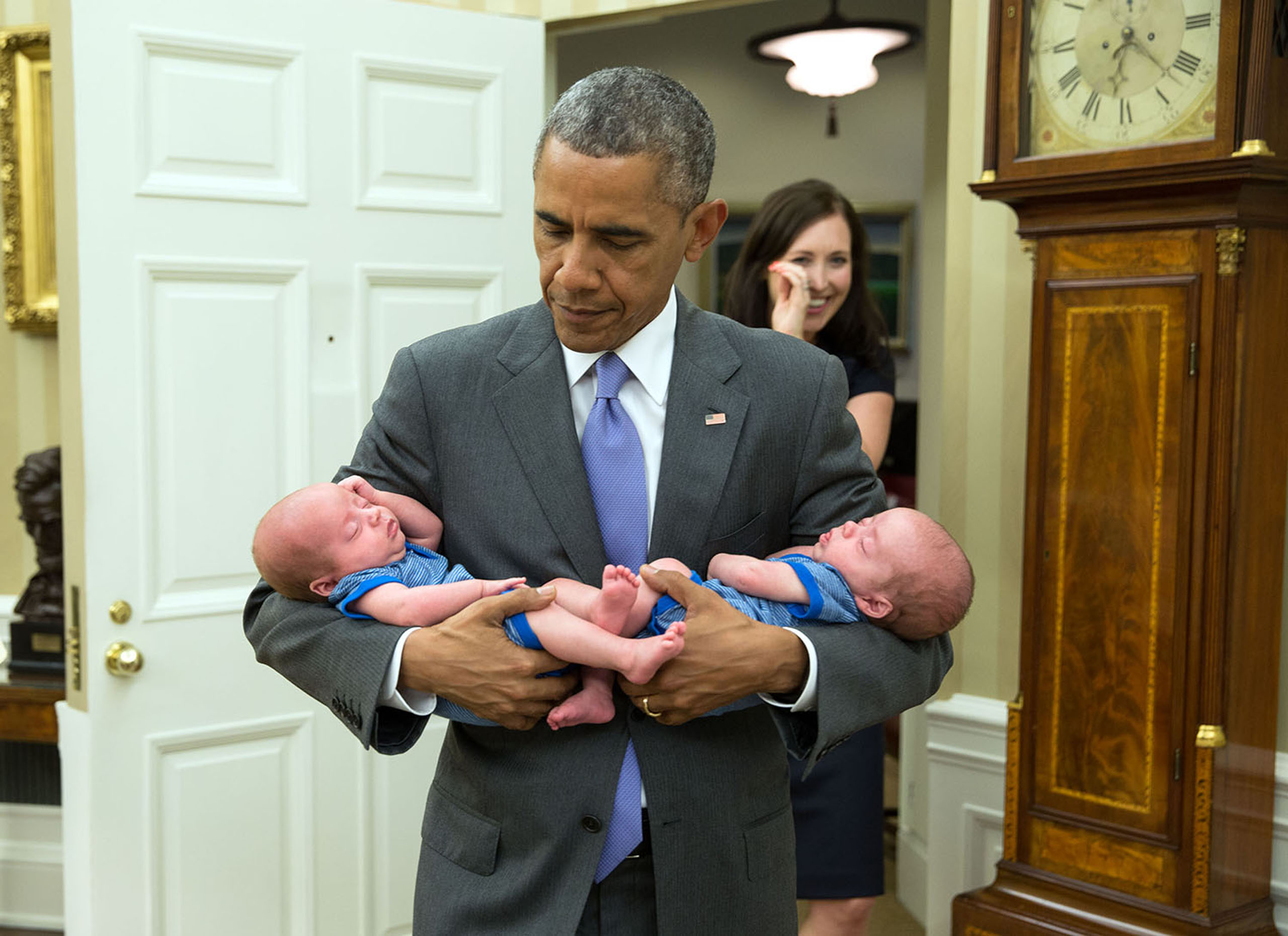 Obama carries the twin boys of Katie Beirne Fallon, Director of Legislative Affairs, into the Oval Office just a few months after they were born on June 17, 2015.