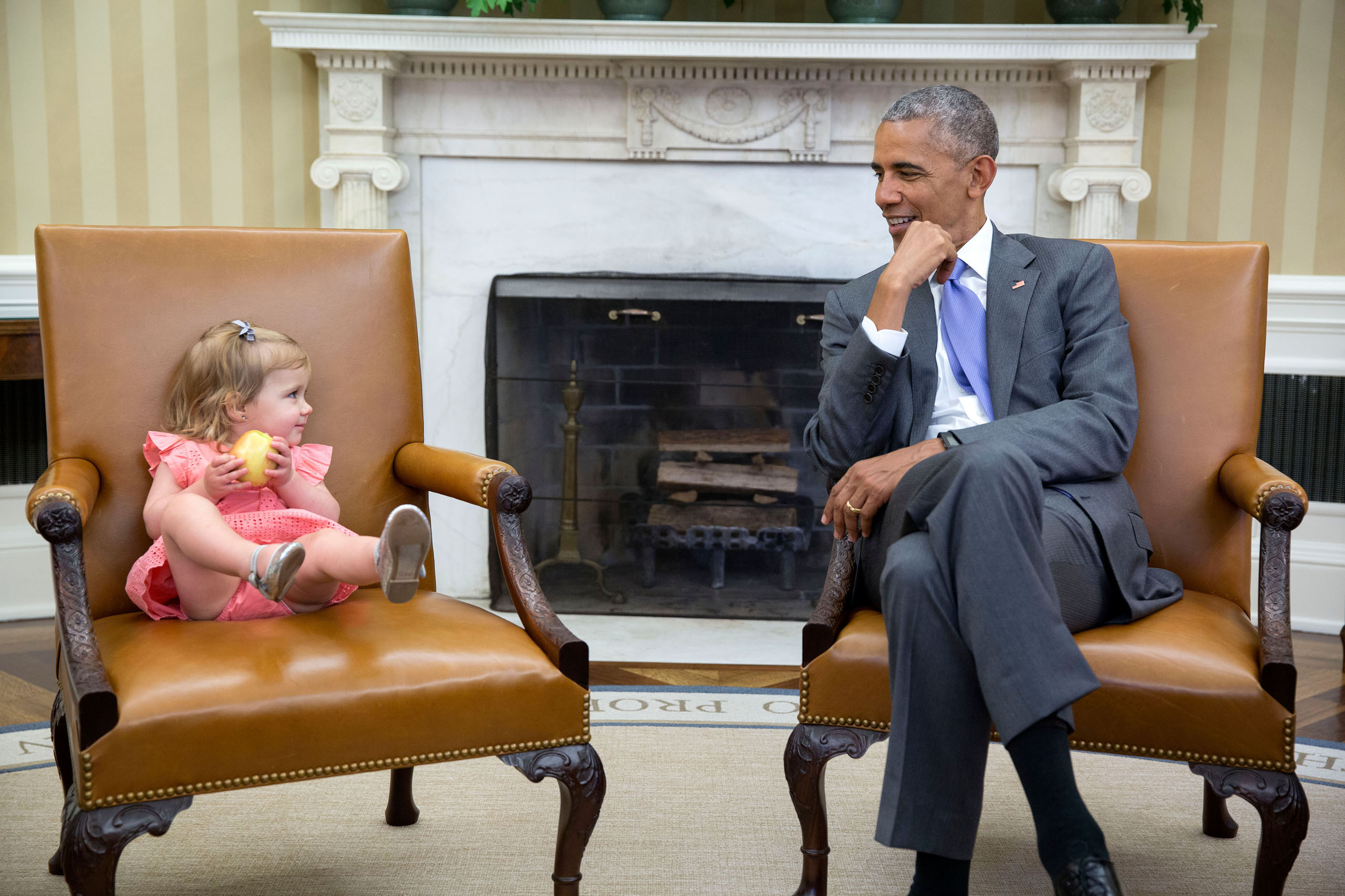 President Barack Obama visits with former adviser David Axelrod's granddaughter, Maelin, in the Oval Office, on June 22, 2016.