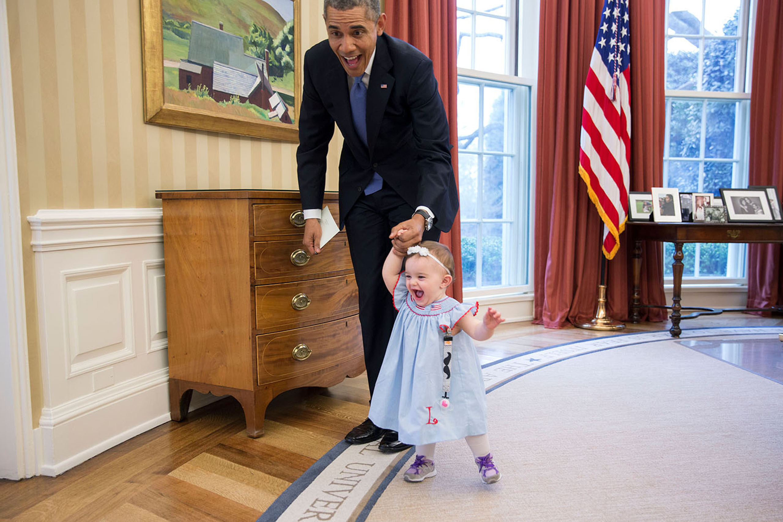 President Barack Obama walks with Lincoln Rose Pierce Smith, the daughter of former Deputy Press Secretary Jamie Smith, in the Oval Office, on April 4, 2014.