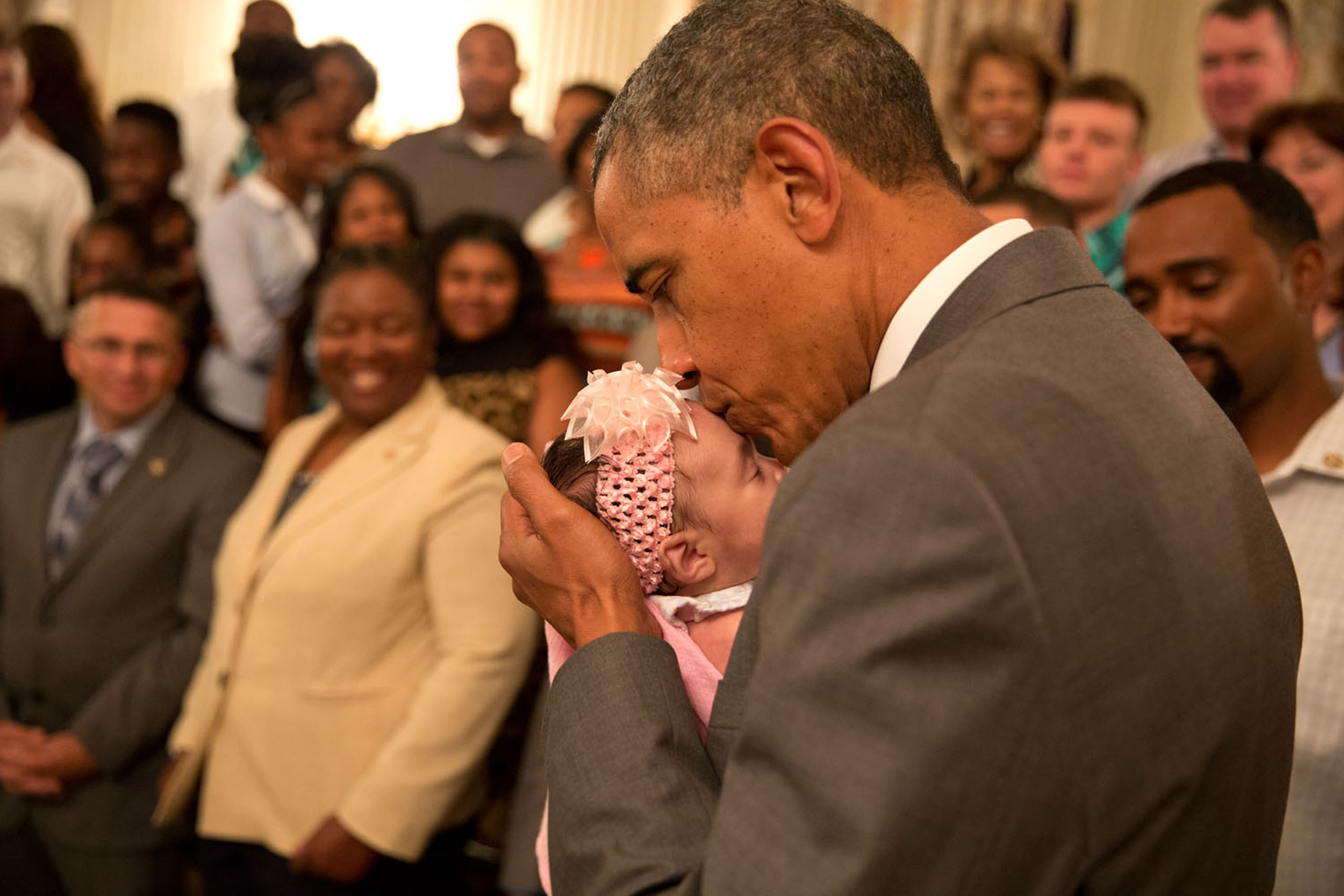 The President kisses a baby girl as he and the Vice President greeted wounded warriors and their families during their tour in the East Room of the White House on June 23, 2014.