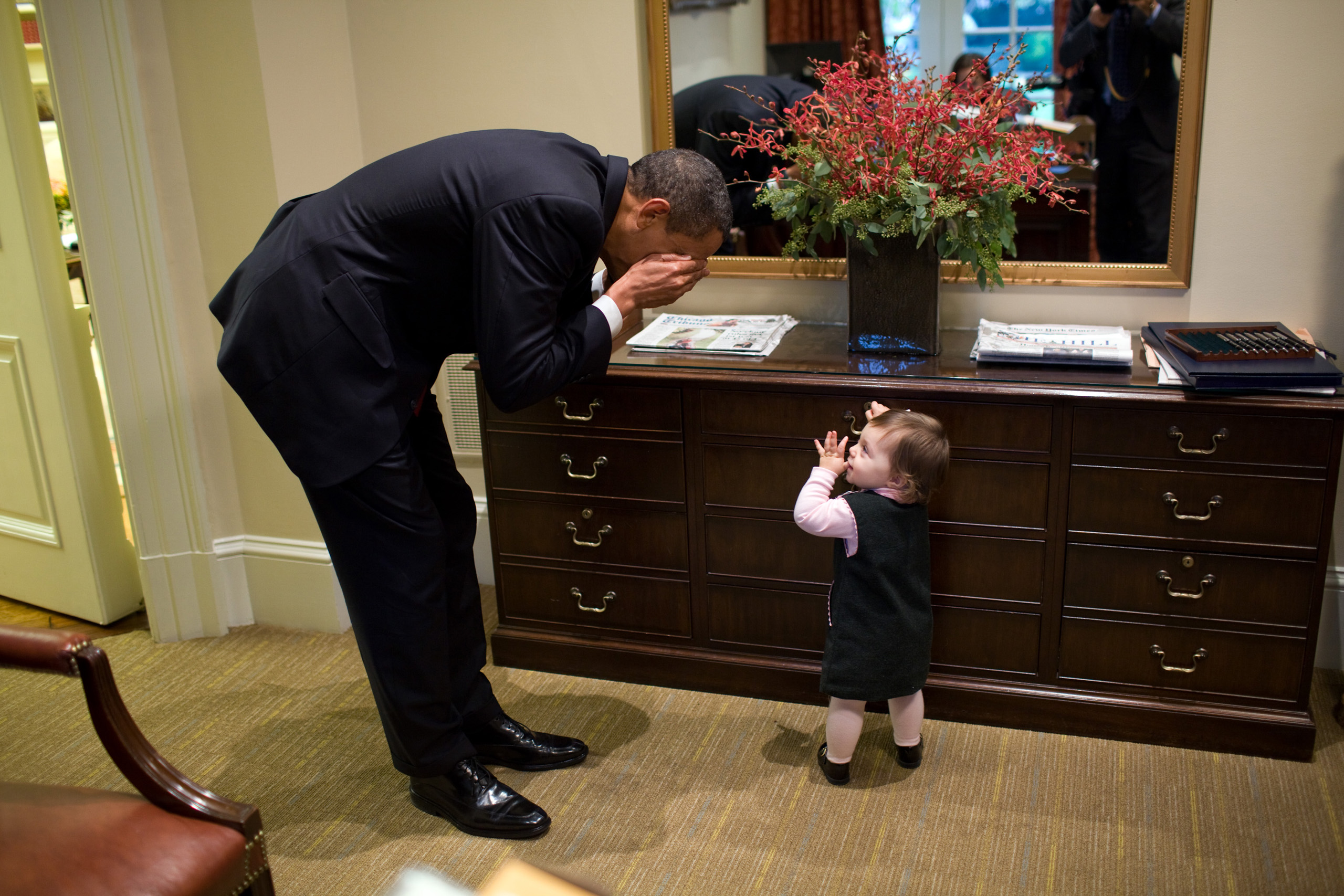 The President plays peek-a-boo with the daughter of White House staffer Emmitt Beliveau in the Outer Oval Office on Oct. 30, 2009.