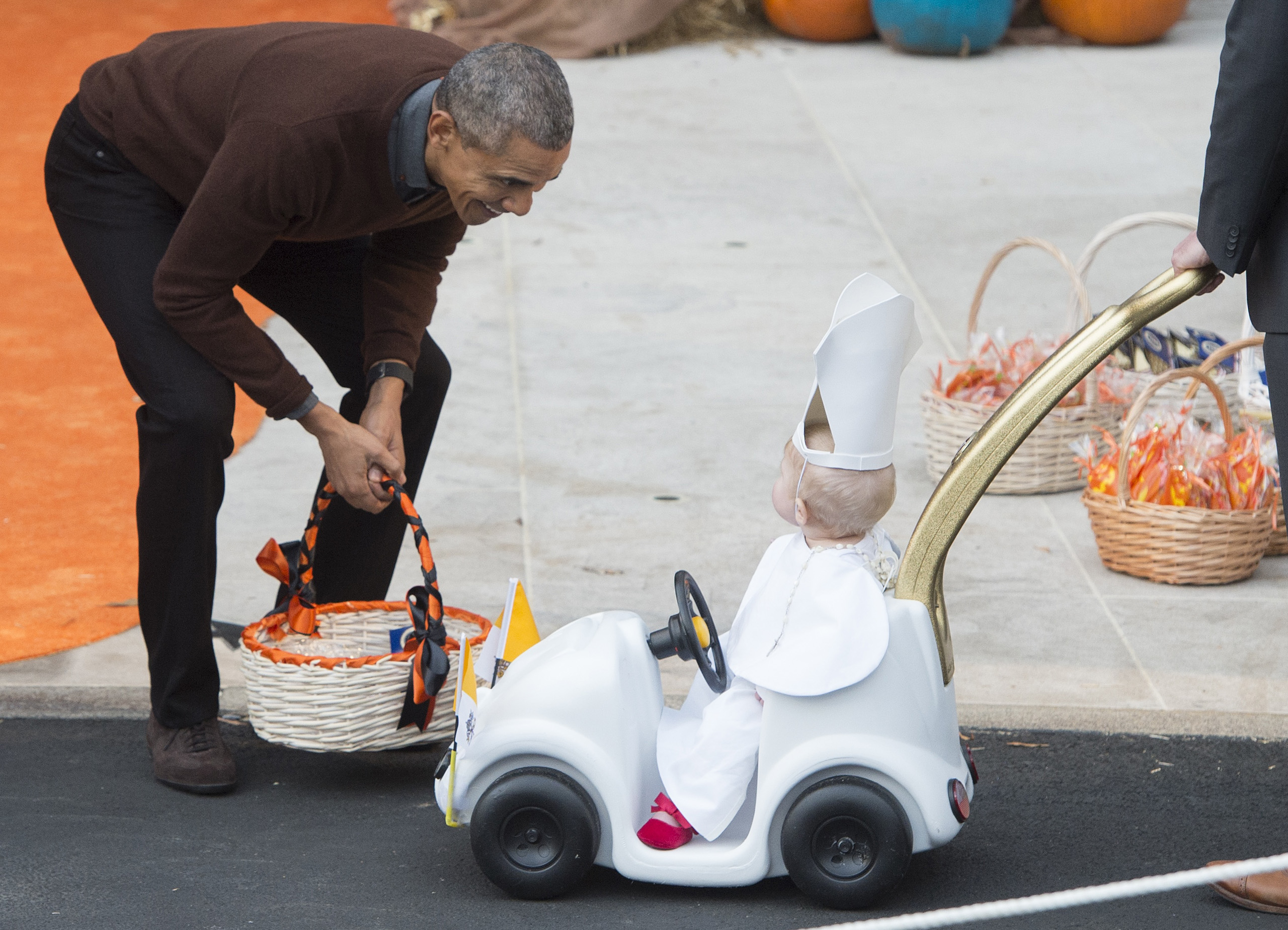 Obama greets a young child dressed as the Pope and riding in a  Popemobile  as he hands out treats to children trick-or-treating for Halloween on the South Lawn of the White House on Oct. 30, 2015.