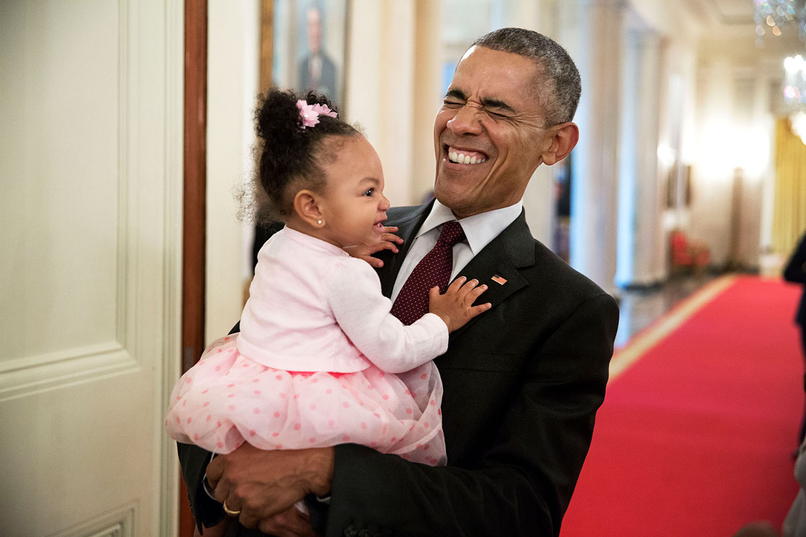 Obama holds the daughter of former staff member Darienne Page Rakestraw in the Cross Hall of the White House, on April 3, 2015.