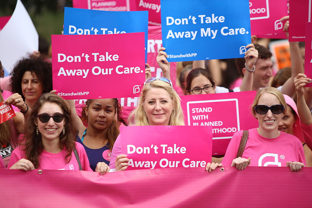 Planned Parenthood supporters hold pink banner and signs.