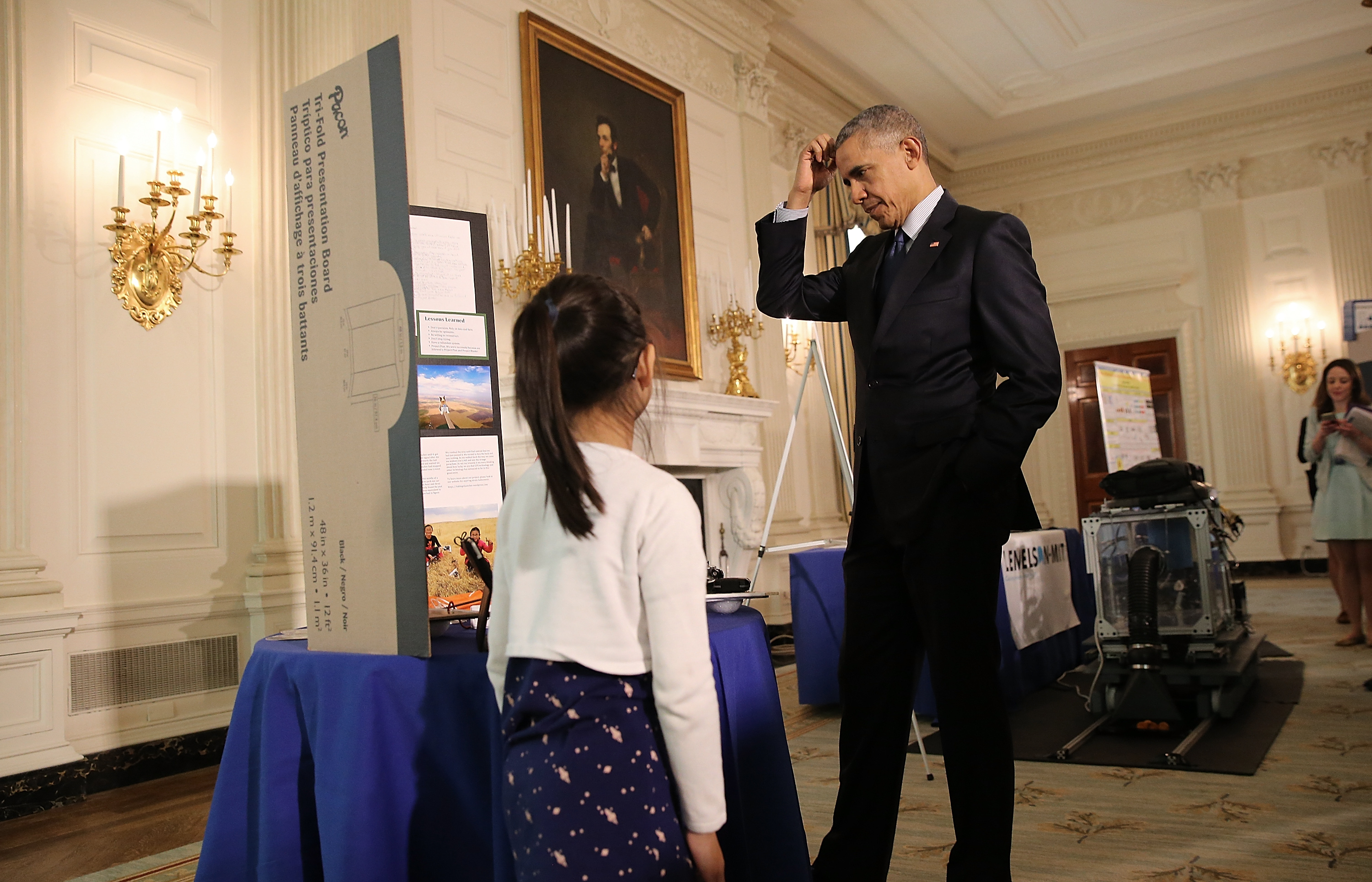 U.S. President Barack Obama listens to sisters Kimberly Yeung (L) and Rebecca Yeung  explain their science project while touring exhibits at the White House Science Fair April 13, 2016 in Washington, D.C.