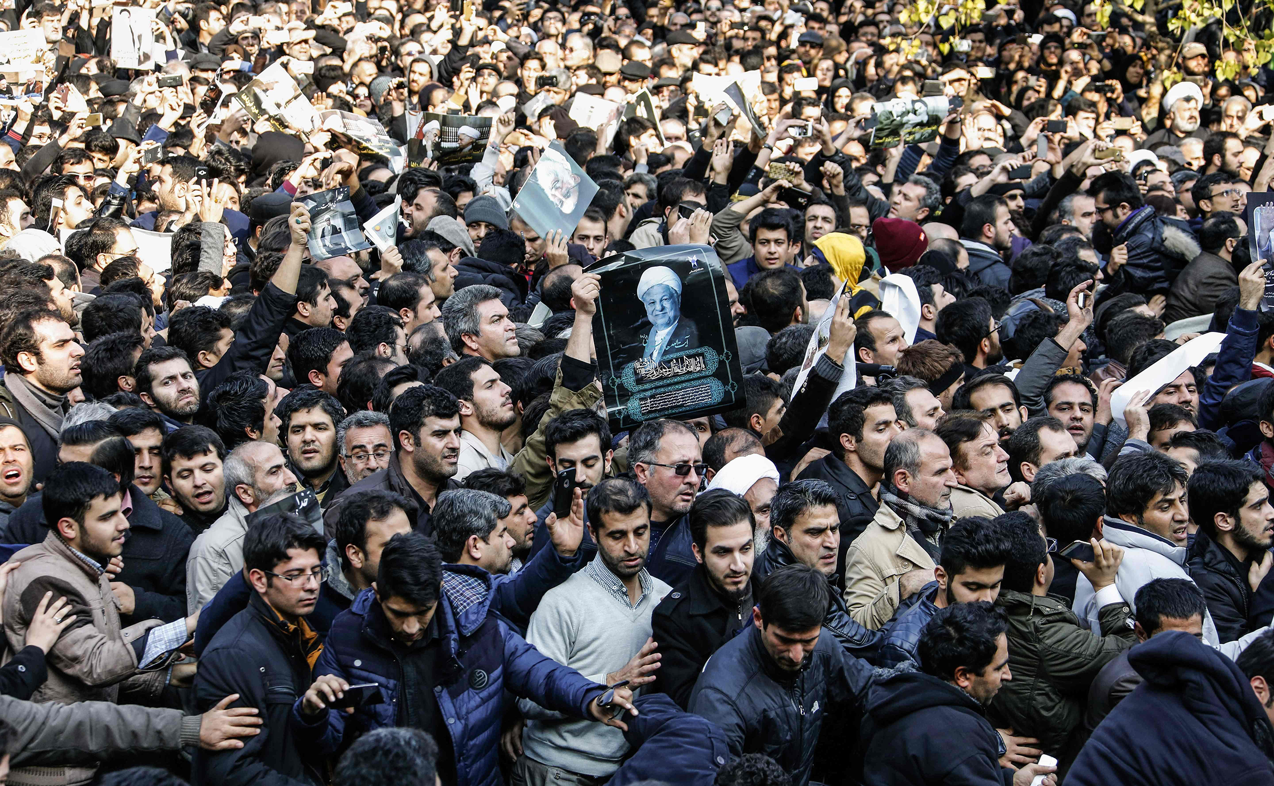 Iranians gather around a hearse carrying the coffin of former President Akbar Hashemi Rafsanjani during his funeral ceremony in Tehran on Jan. 10, 2017.                   The heavyweight politician will be buried inside the crypt of Ayatollah Ruhollah Khomeini, the leader of Iran's 1979 Islamic revolution, at Khomeini's mausoleum.