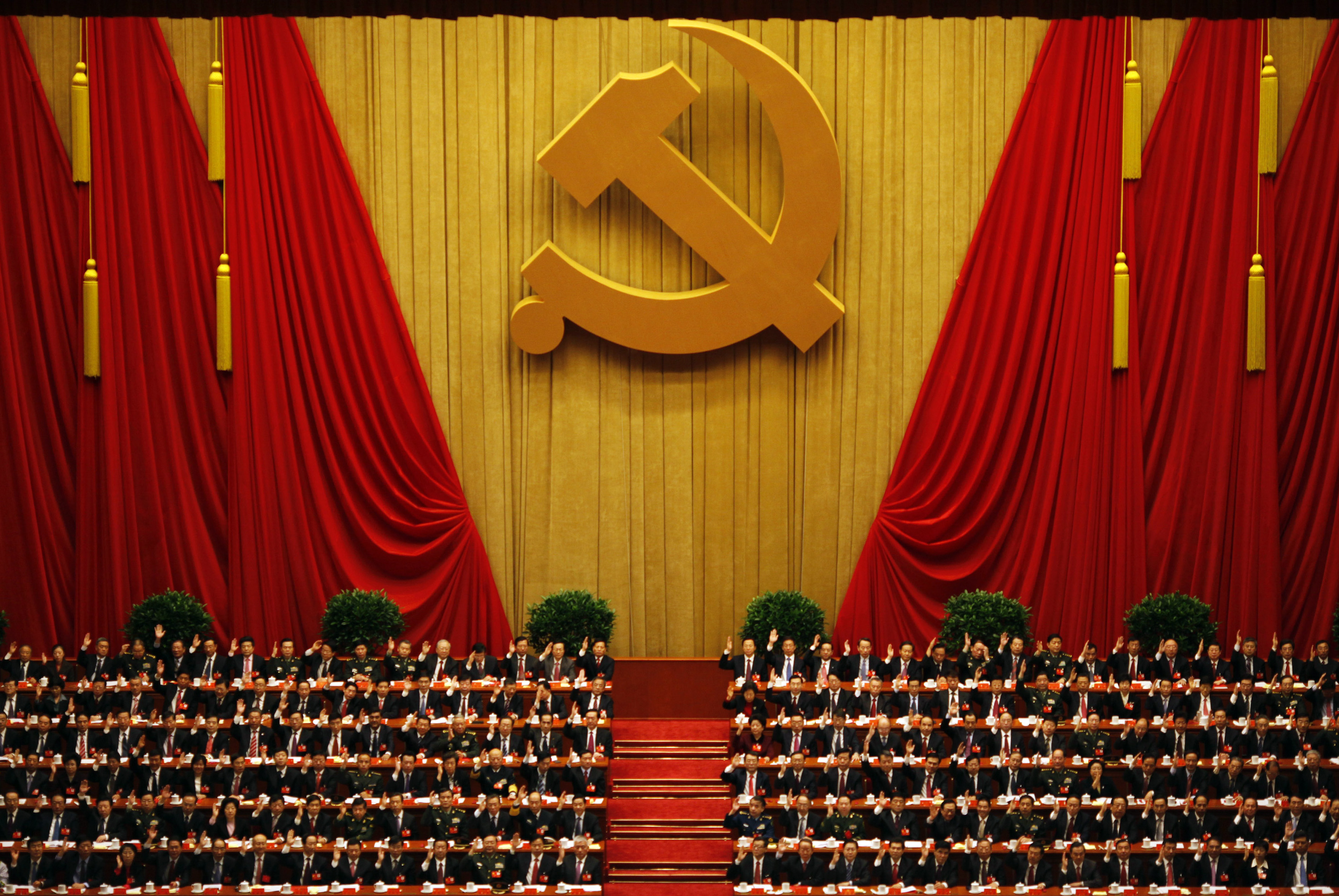 A general view shows delegates raising their hands as they take a vote at the closing session of the 18th National Congress of the Communist Party of China at the Great Hall of the People in Beijing on Nov. 14, 2012