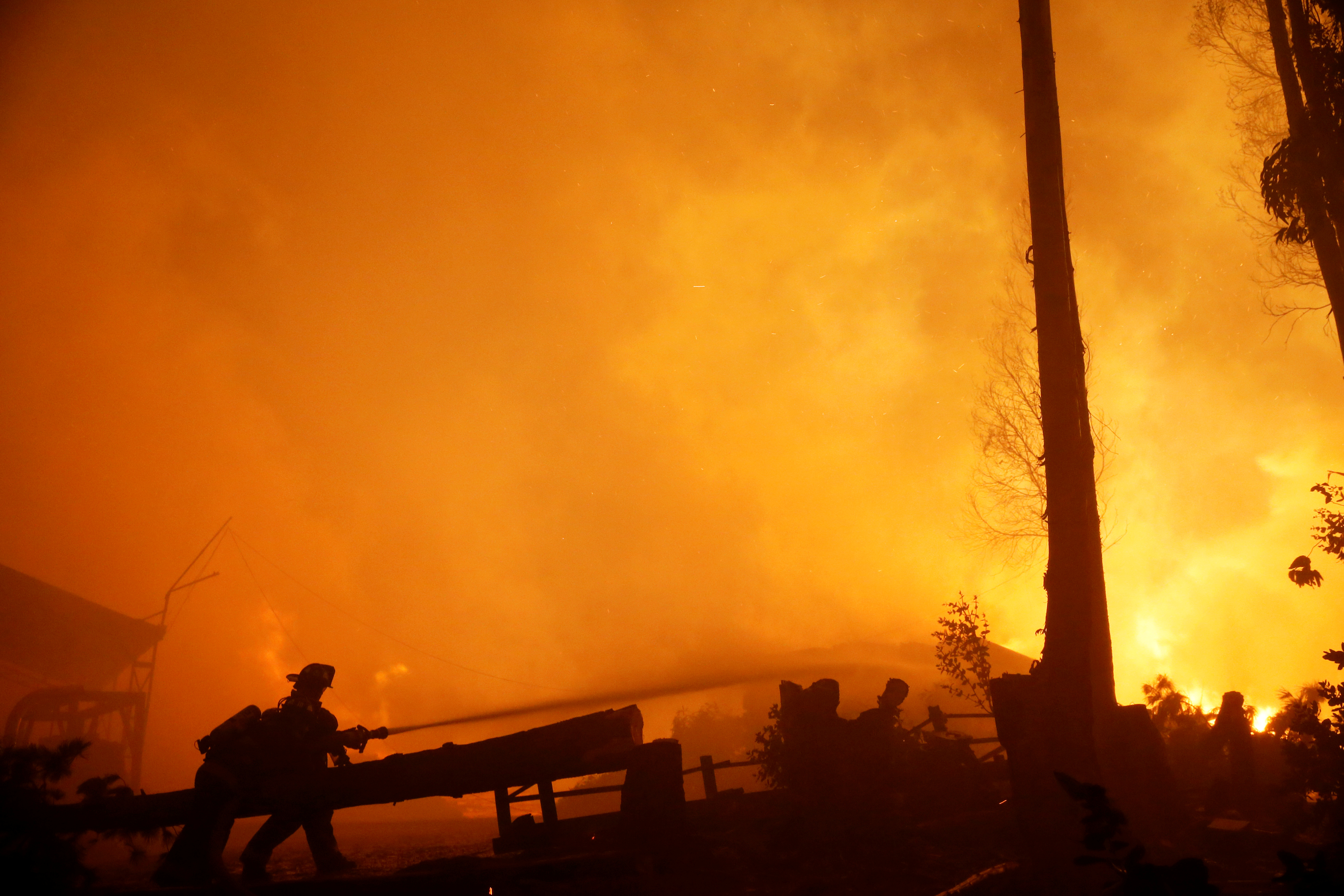 Firefighters try to stop a fire as the worst wildfires in Chile's modern history ravage wide swaths of the country, in Santa Olga, Chile Jan. 26, 2017.