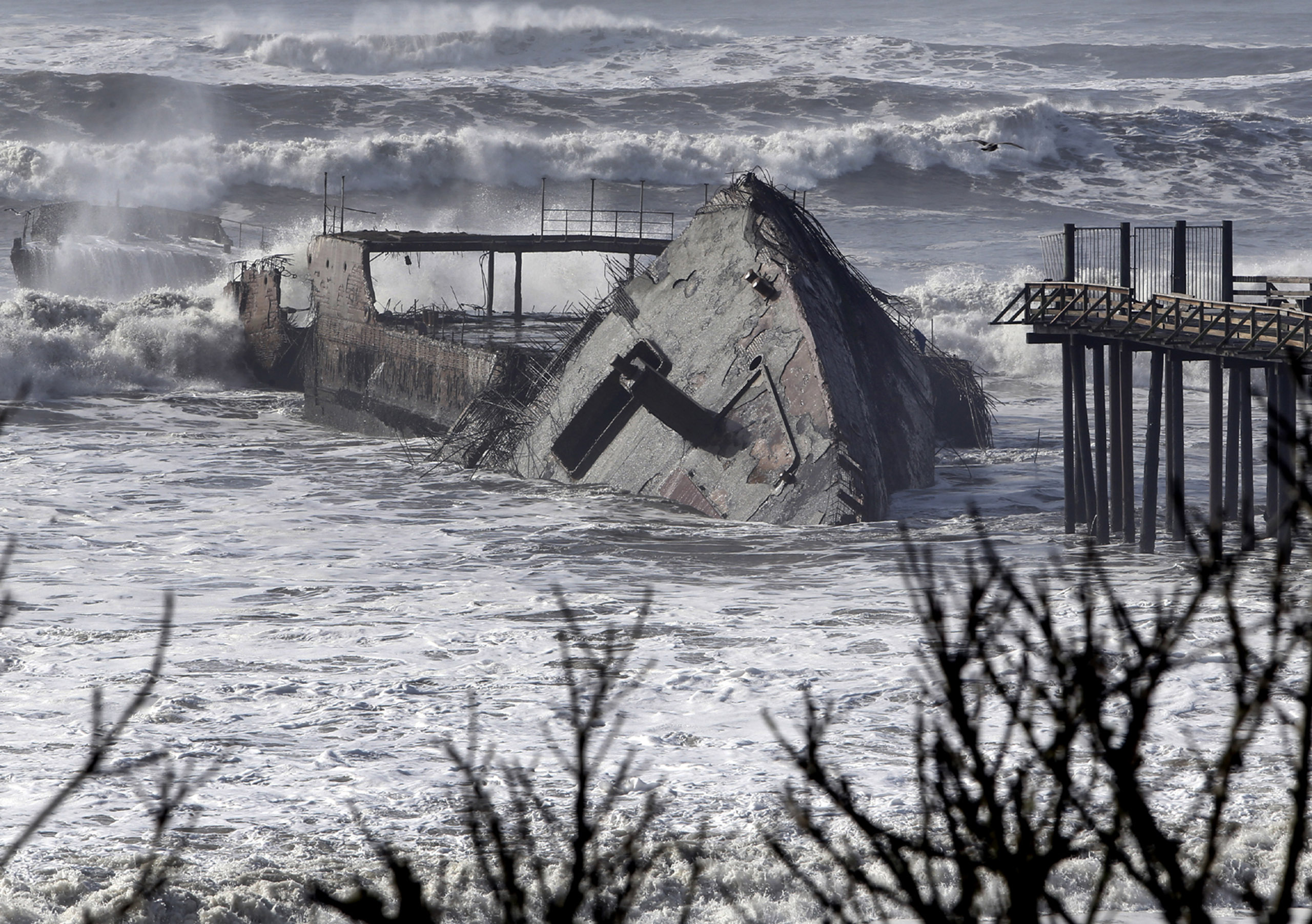 Waves crash into the historic WW1-era ship called S.S. Palo Alto at Rio Del Mar in Aptos, Calif., on Jan. 21, 2017.