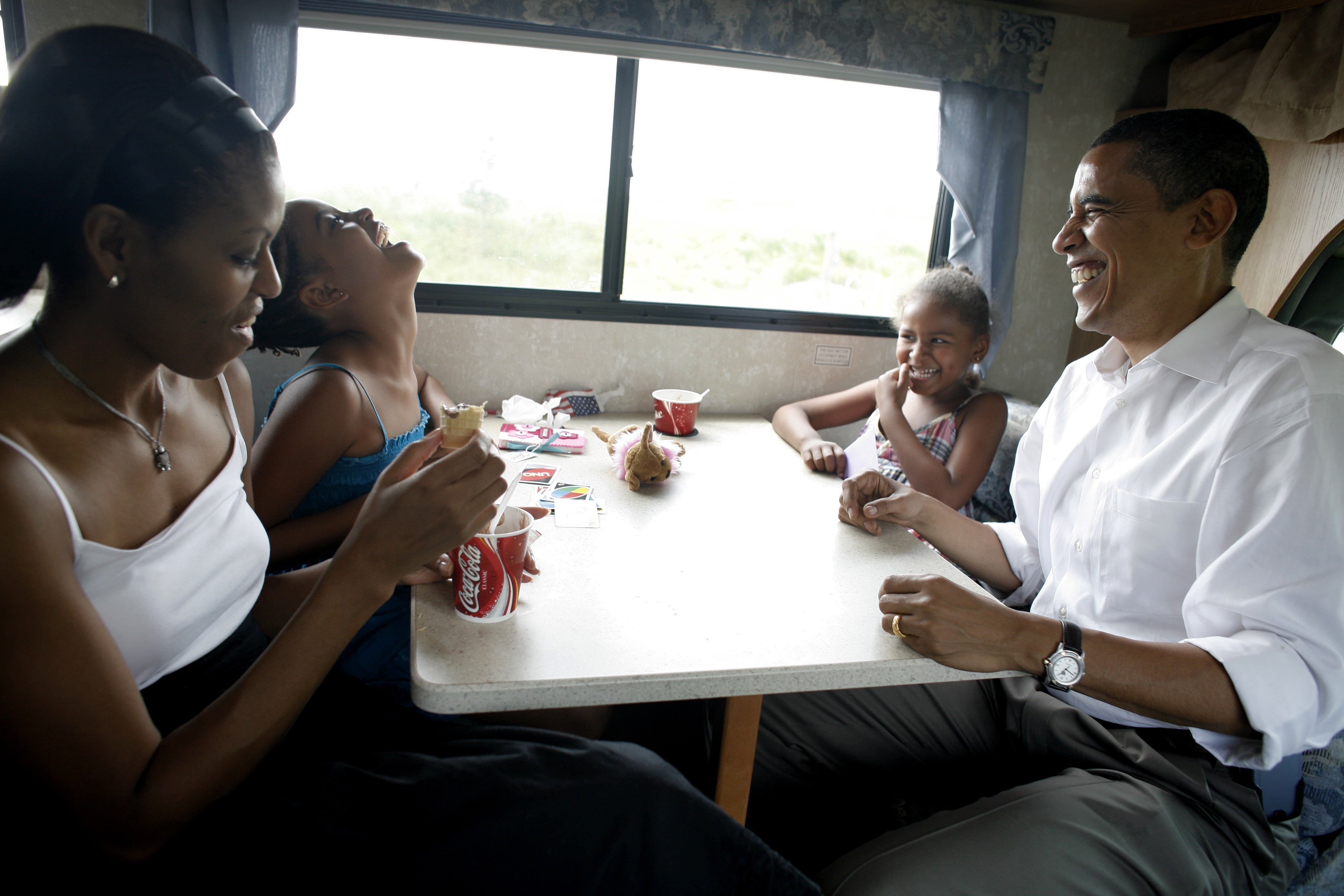 Then-Democratic presidential hopeful Senator Barack Obama, his wife Michelle and two daughters Sasha, 6, and Malia, 9, play cards in their RV on a campaign swing between Oskaloosa and Pella, Iowa, on July 4, 2007.