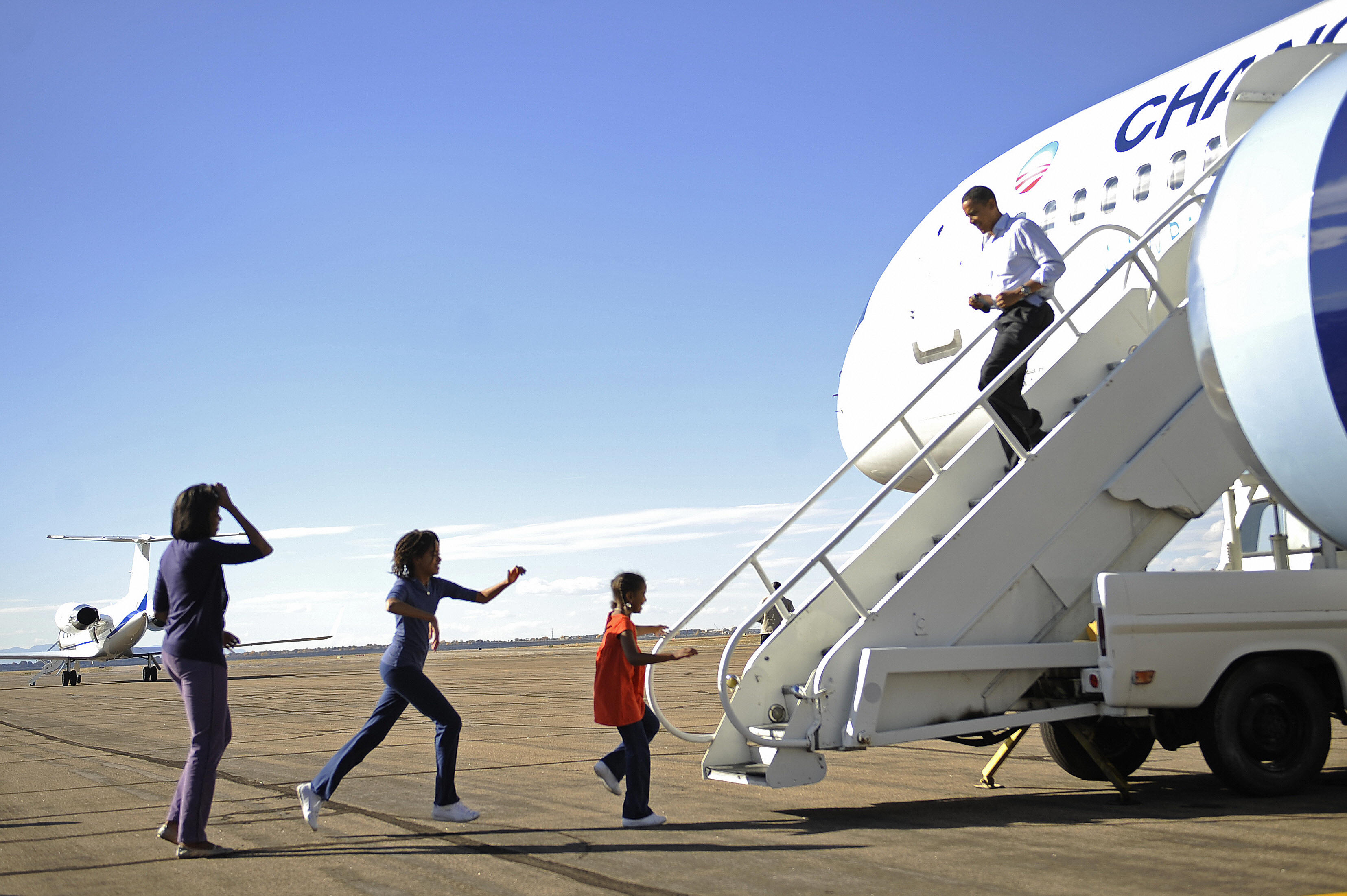 Then-Democratic presidential candidate Senator Barack Obama is welcomed by his wife Michelle and daughters Malia, 11 and Sasha, 7, upon landing in Pueblo, Colorado, on Nov. 01, 2008.