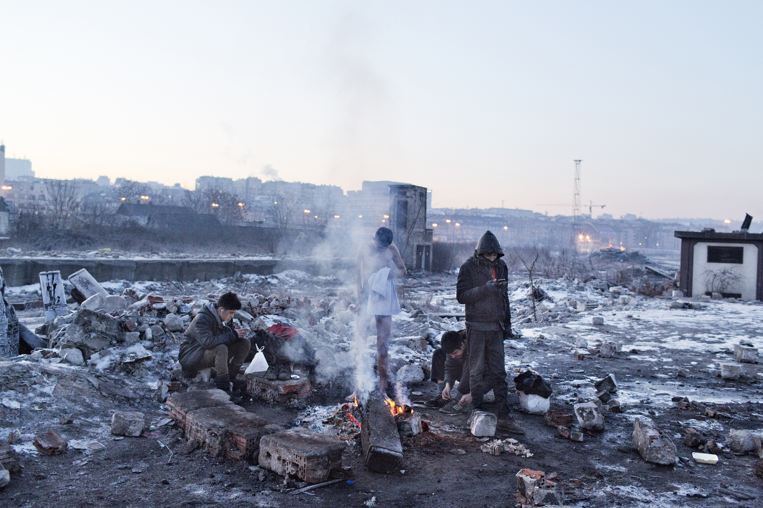 A group of unaccompanied minors from Afghanistan, including a disabled boy,  keep warm by a fire near the train station of Belgrade, Serbia, Jan 15, 2017.
