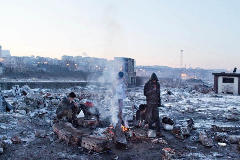 A group of unaccompanied minors form afghanistan , include a boy with disability, to keeps warm by starting a makeshift fire near the train station of Belgrade, Jan 15, 2017.