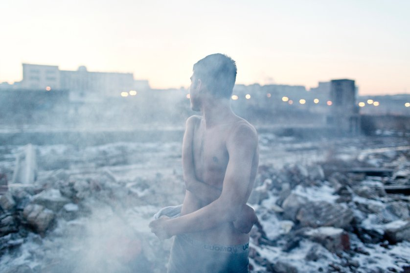 Abdul, 16, an unaccompanied minor from Afghanistan showers near a makeshift shelter in an abandoned warehouse  Belgrade.
