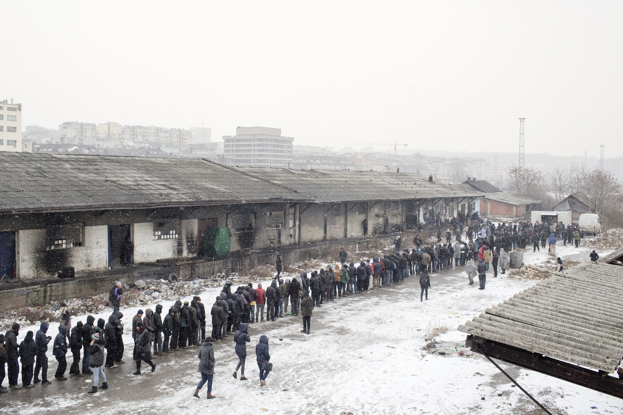 Migrants line up for food distributed by volunteers outside of derelict warehouses which are being used for shelter, Belgrade, Serbia, Jan. 17, 2017. Temperatures fell below 32F in the night.