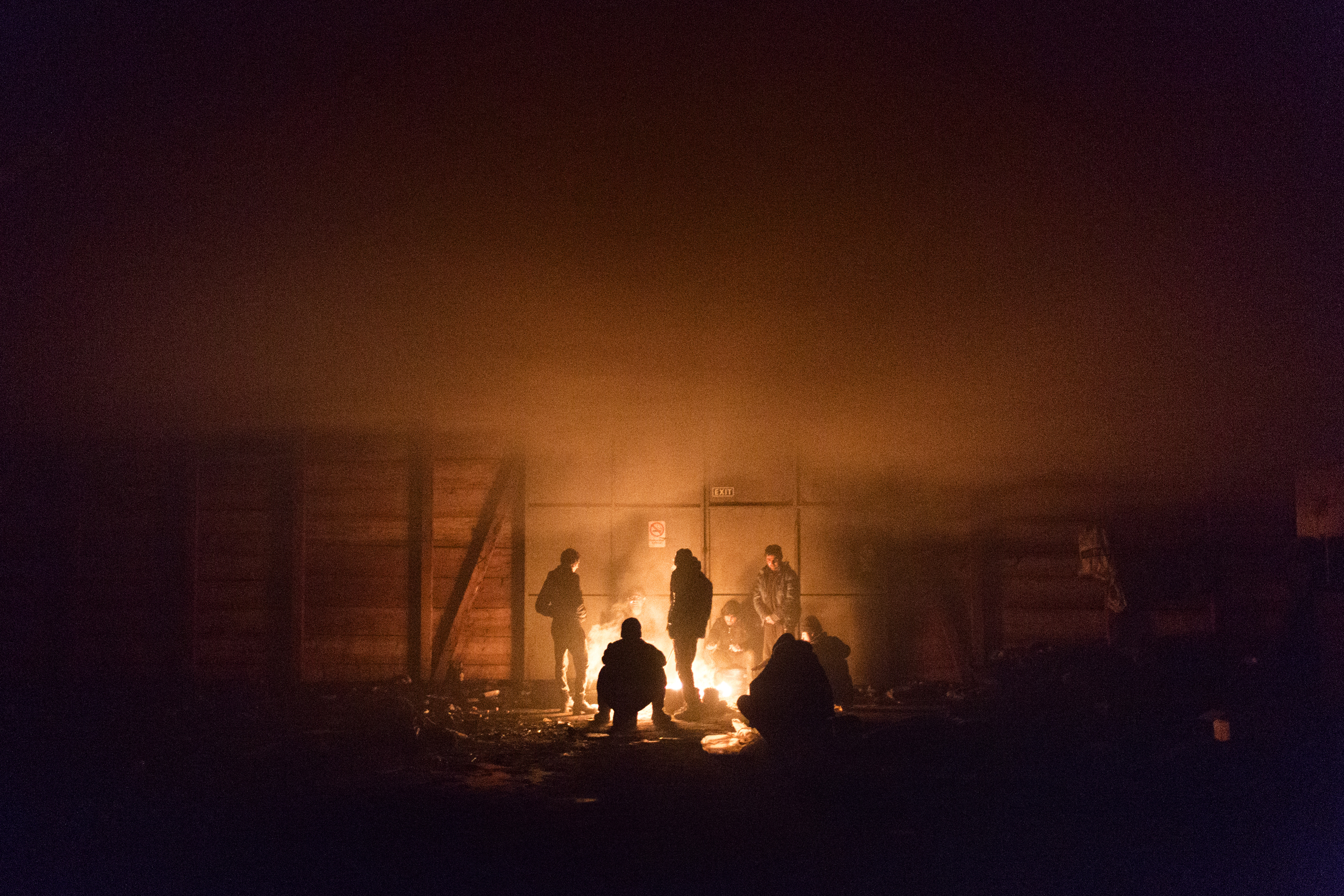A group of unaccompanied minors from Afghanistan try to keep warm near a fire in an abandoned warehouse, Belgrade, Serbia, Jan. 14, 2017.