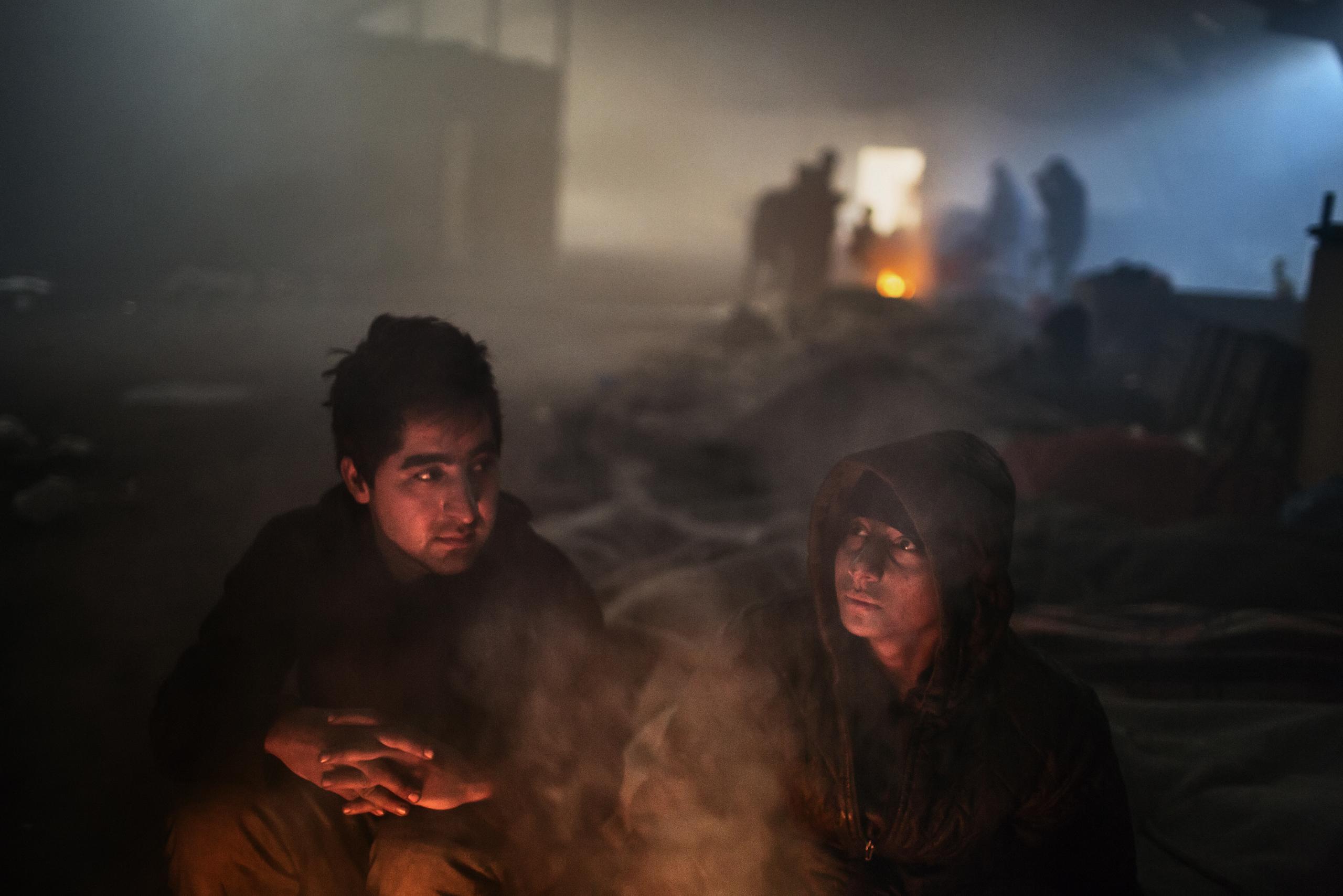 Two unaccompanied minors from afghanistan stay warm inside an abandoned warehouse in Belgrade, Jan 13, 2017.