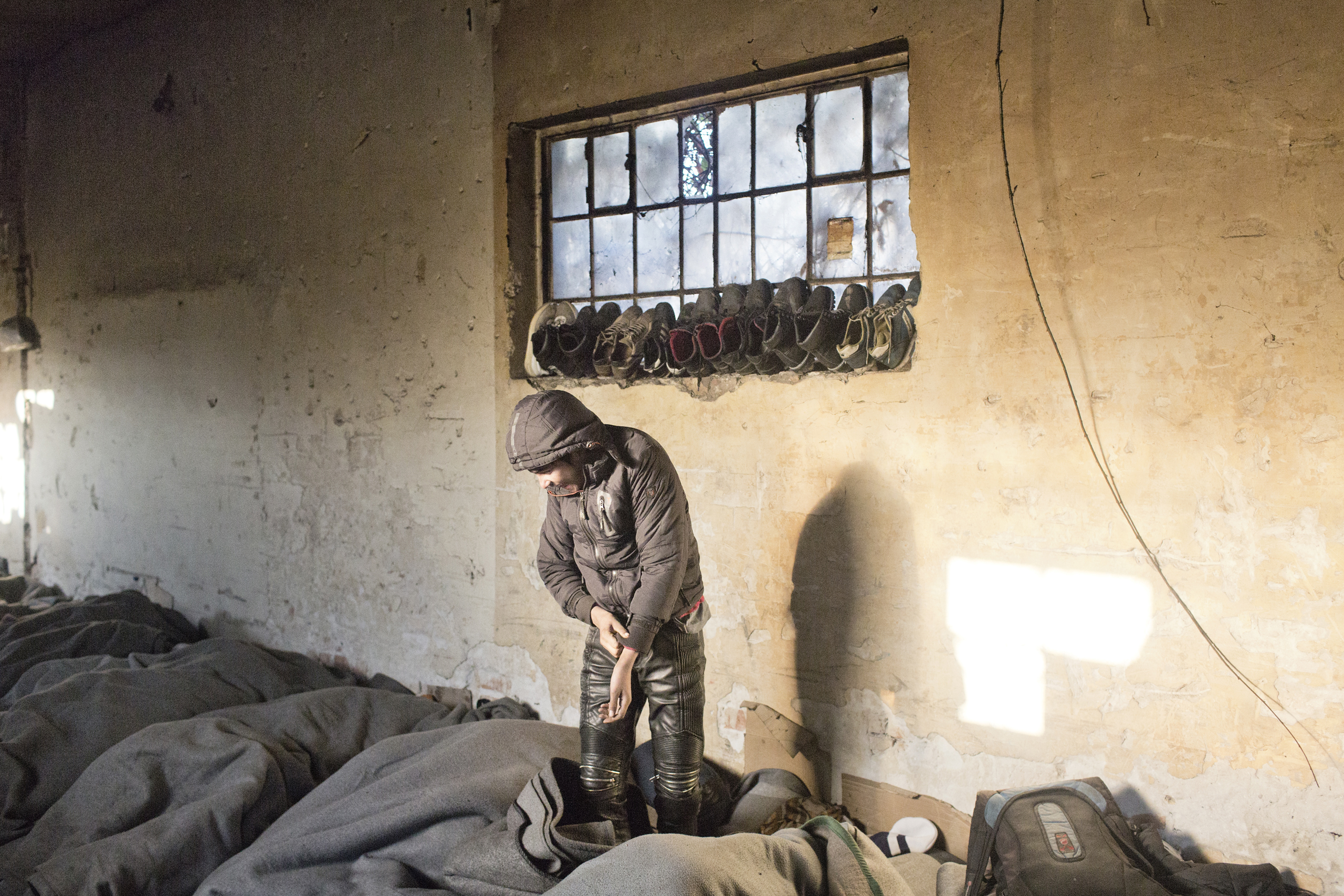 Unaccompanied minors wake up early in the morning in an abandoned warehouse  in central Belgrade, Serbia. They will have to pay thousands of euros to smugglers help them leave and enter the European Union, Jan. 2017.