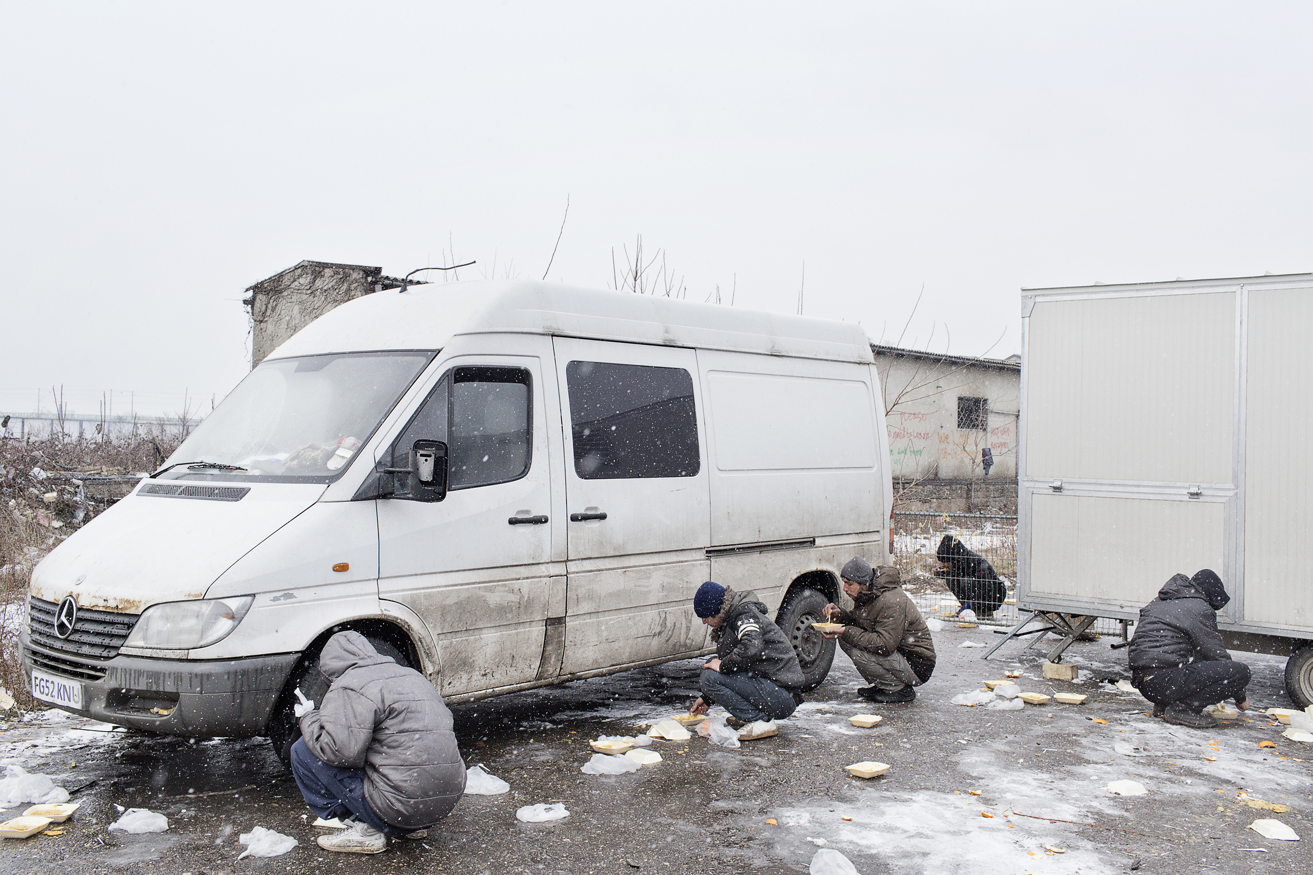 Migrants eat hot meals received from volunteers, outside of a derelict warehouse which they use as a makeshift shelter, Belgrade, Serbia,  Jan 17, 2017.