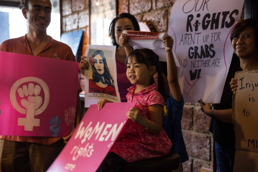 "A young Thai girl holds a ""women's rights are human rights"" sign at Roadhouse BBQ restaurant where many of the Bangkok Women's March participants gathered on January 21, 2017 in Bangkok, Thailand."