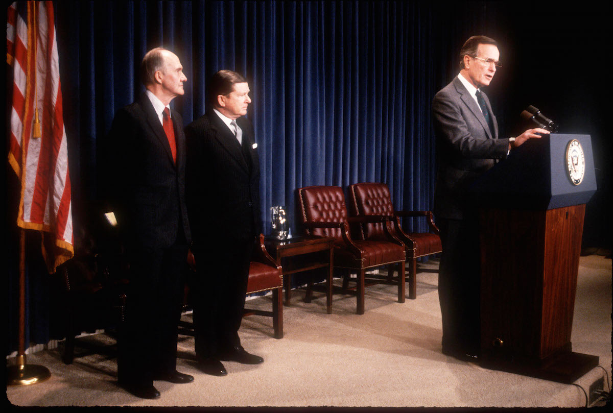 National Security Advisor Brent Scowcroft stands next to John Tower as Vice President George Bush announces the former Senator's nomination for Secretary of Defense on Dec. 16, 1988 in Washington, D.C.