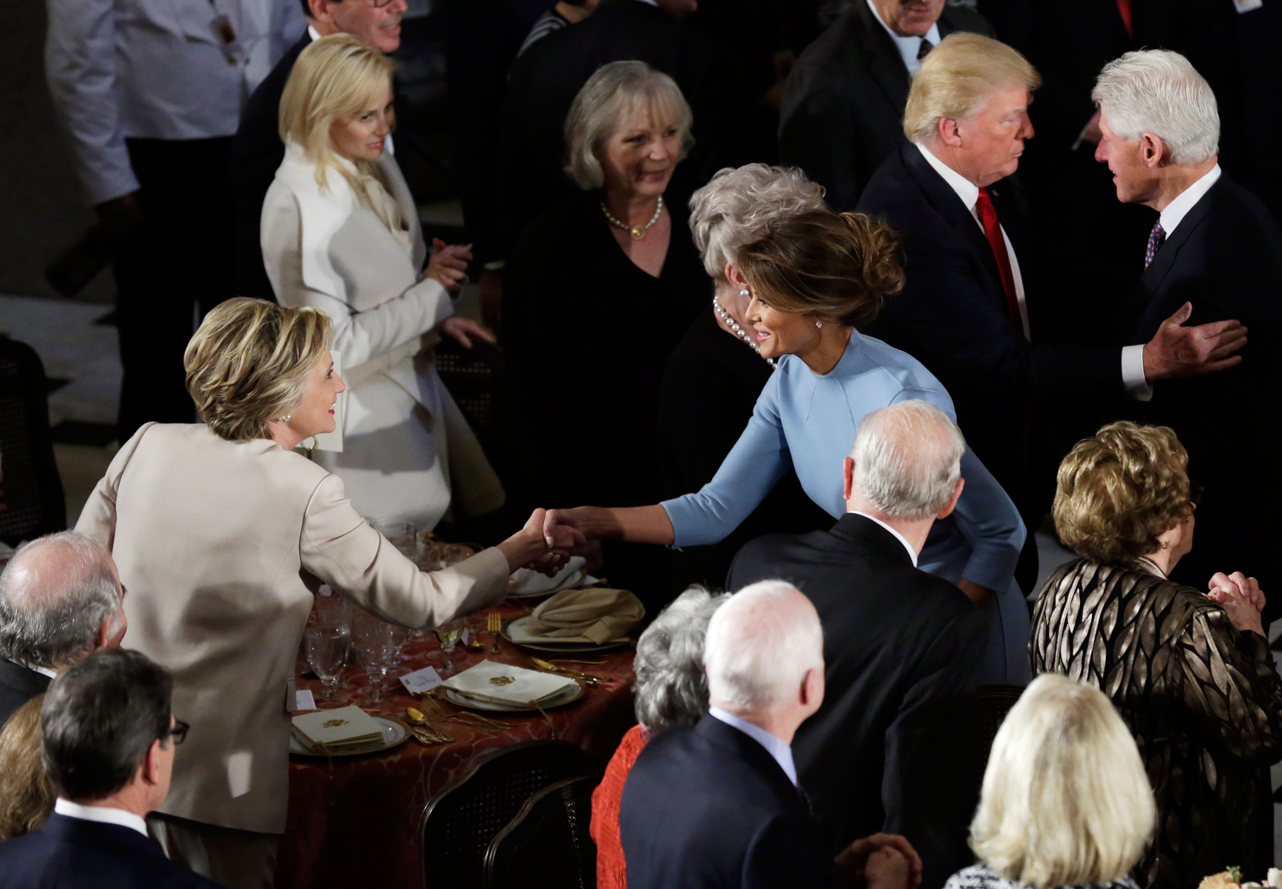 Former Democratic U.S. presidential nominee Hillary Clinton greets First lady Melania Trump as her husband Bill Clinton speaks with President Donald Trump during the Inaugural luncheon at the National Statuary Hall in Washington on Jan. 20, 2017.