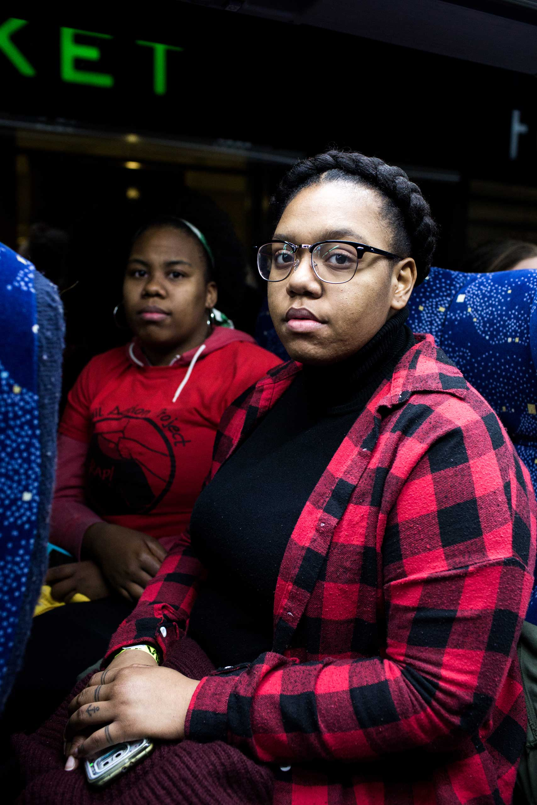 1:38 AM: Lysondra Webb, 25, (right) and Sade Dixon, 25, (left) pose for a portrait on the bus.  As a member of a marginalized community I'm obligated to be a representative,  Lysondra tells me.  That person who's going to be sitting in the White House and all his cronies are not for me.                                                                 My grandparents protested with Malcolm X for me to have a better life. It's my duty to continue the fight and its' sad that I have to but I will fight and speak up for my brothers and my community,  says Dixon.