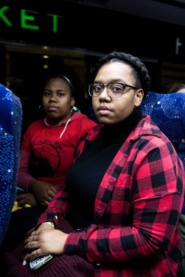 "1:40 AM: Lysondra Webb, 25, (right) and Sade Dixon, 25, (left) pose for a portrait on the bus. As a member of a marginalized community I'm obligated to be a representative,"" Lysondra tells me. ""That person who's going to be sitting in the White House and all his cronies are not for me."" ""My grandparents protested with Malcolm X for me to have a better life. It's my duty to continue the fight and its' sad that I have to but I will fight and speak up for my brothers and my community,"" says Dixon."