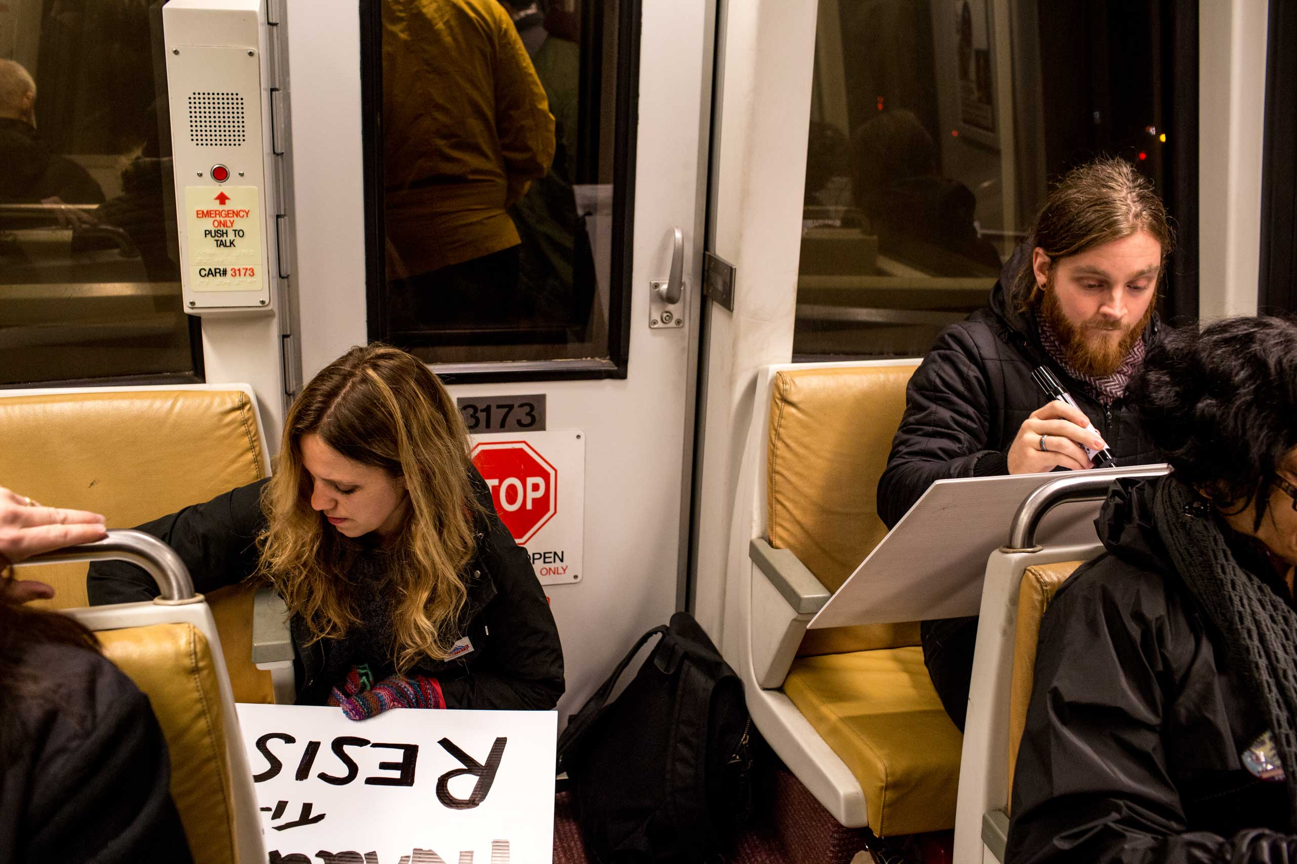 6:12 AM: Anna and Andrew finish their signs on the metro. Other protesters join the members of Answer Coalition, mingling and chatting with each other, while some mumble about how much they need coffee. Trump supporters are also riding the metro. The two groups stare at each other awkwardly in the early morning.