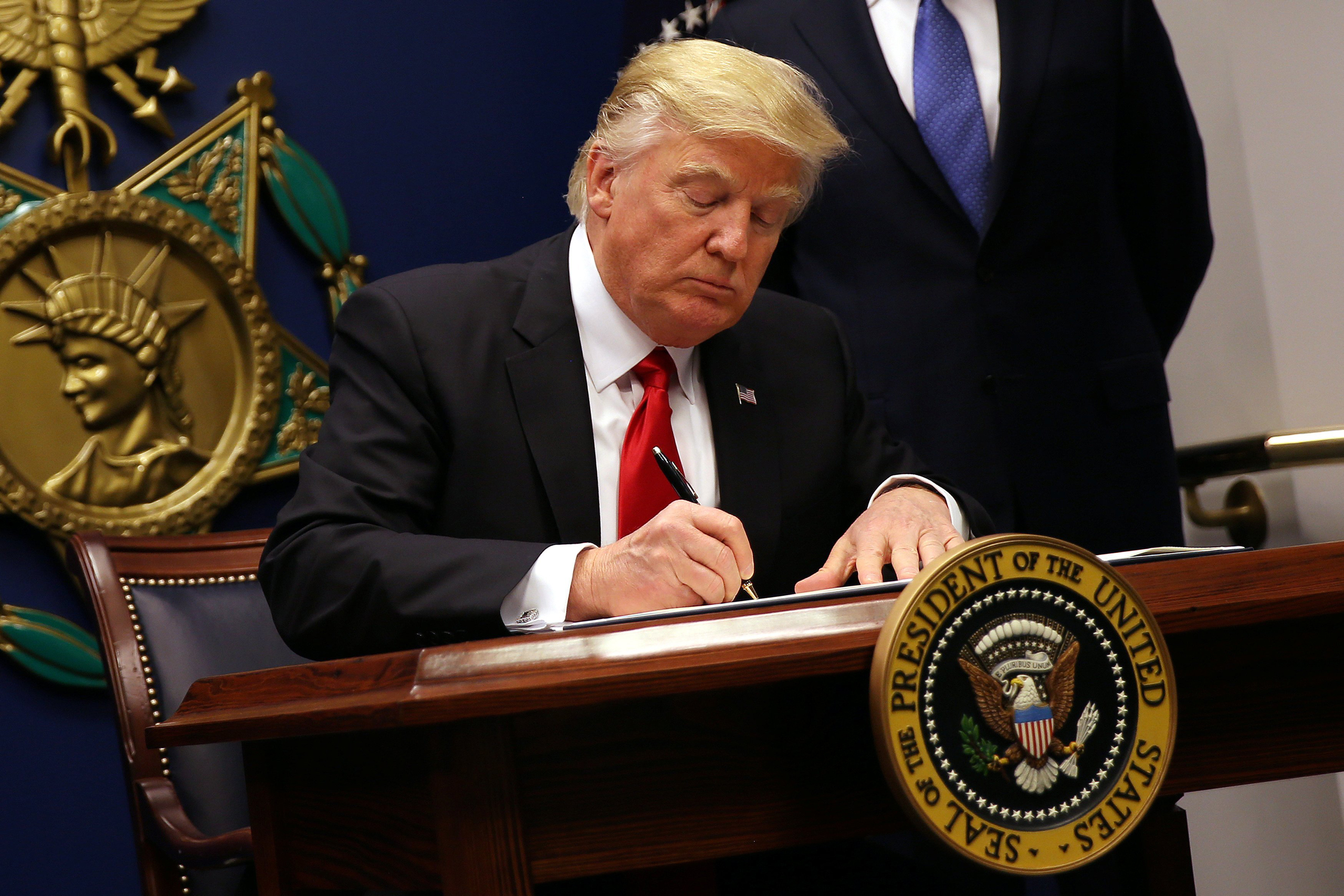 President Donald Trump signs an executive order imposing a four-month travel ban on refugees entering the United States and a 90-day hold on travelers from Syria, Iran and five other Muslim-majority countries at the Pentagon in Washington on Jan. 27, 2017.