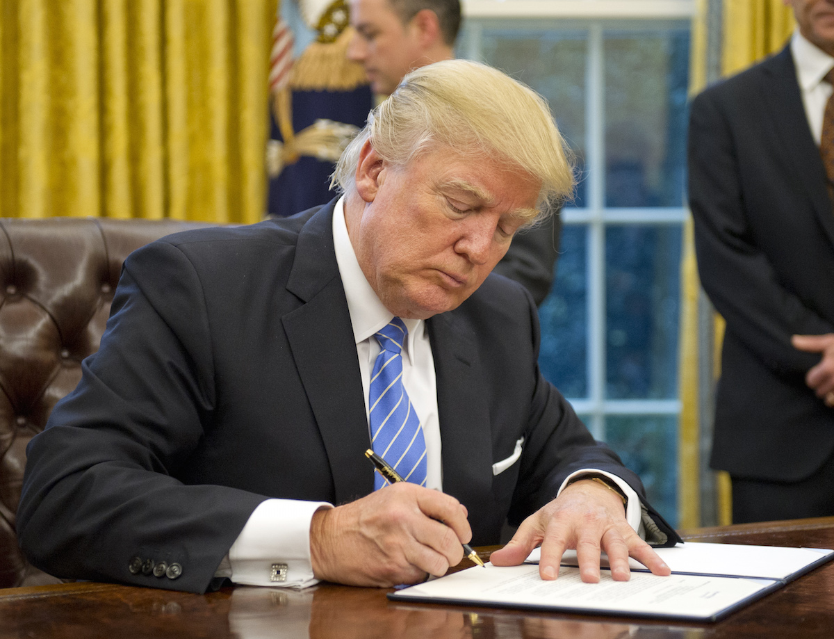 U.S. President Donald Trump signs an executive order in the Oval Office of the White House in Washington, D.C., U.S., on Jan. 23, 2017.