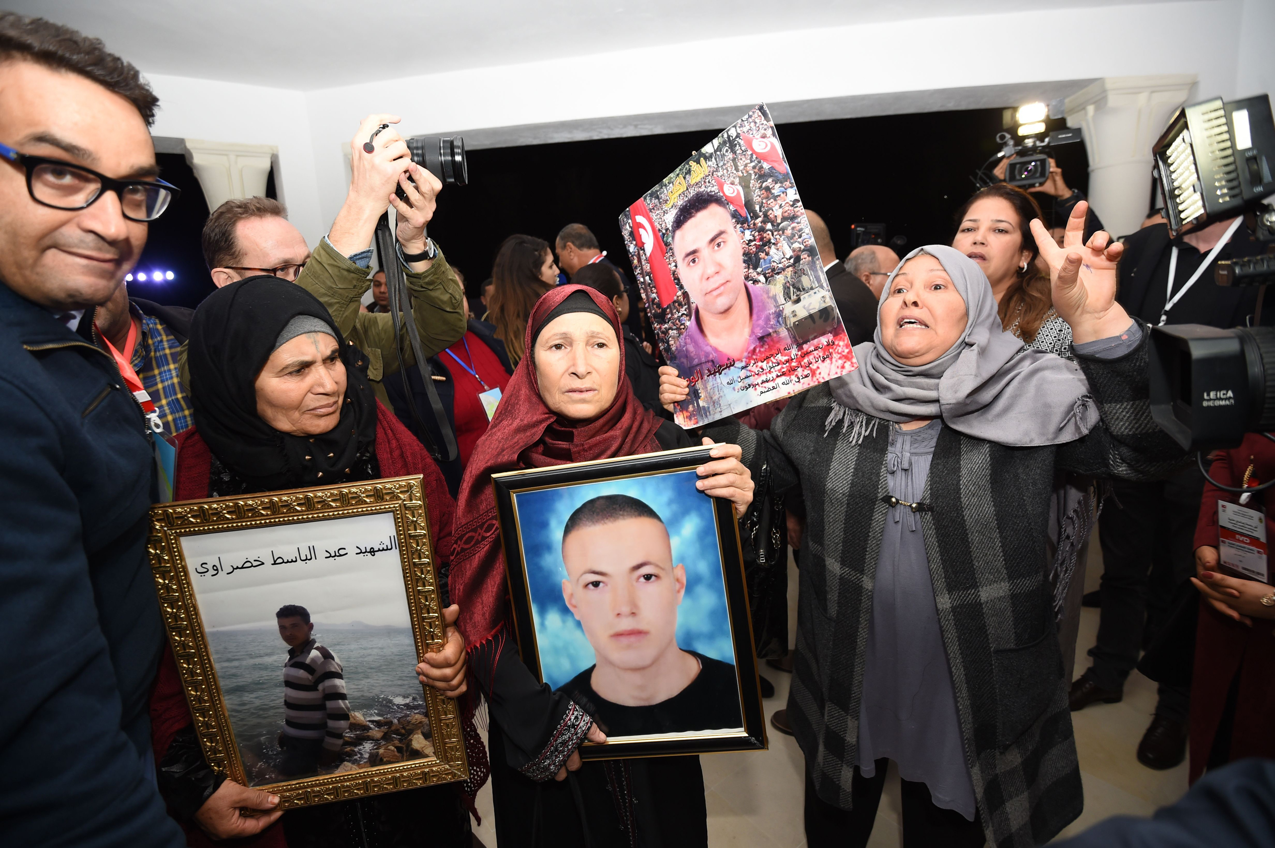 Tunisian mothers of a torture victims carry their sons' portraits as they arrive for a hearing before the The Truth and Dignity Commission (IVD) in Tunis on Nov. 17, 2016.