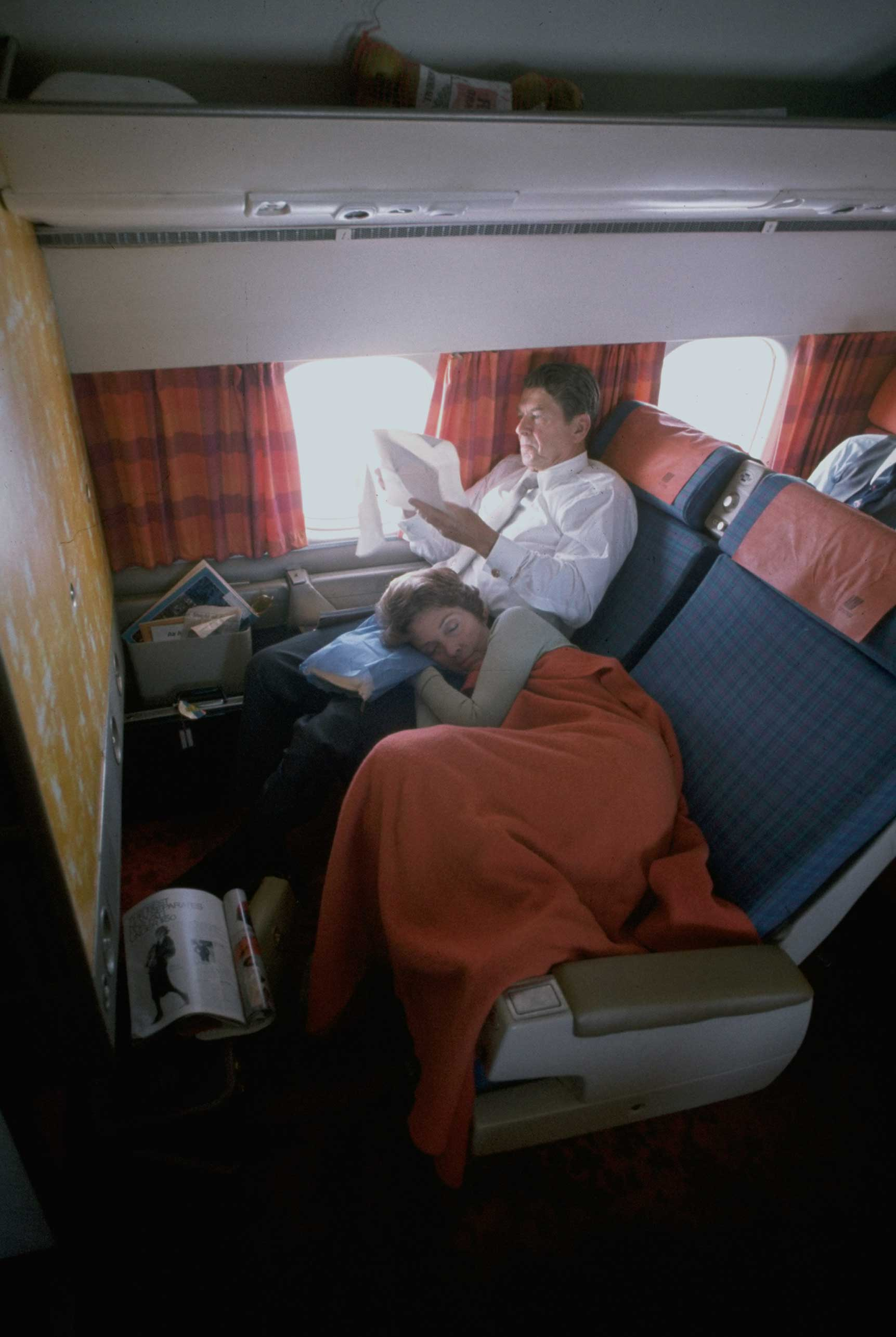 Nancy Reagan sleeping while resting her head in her husband's lap as they fly en route from West Virginia to Los Angeles while campaigning for the presidency.