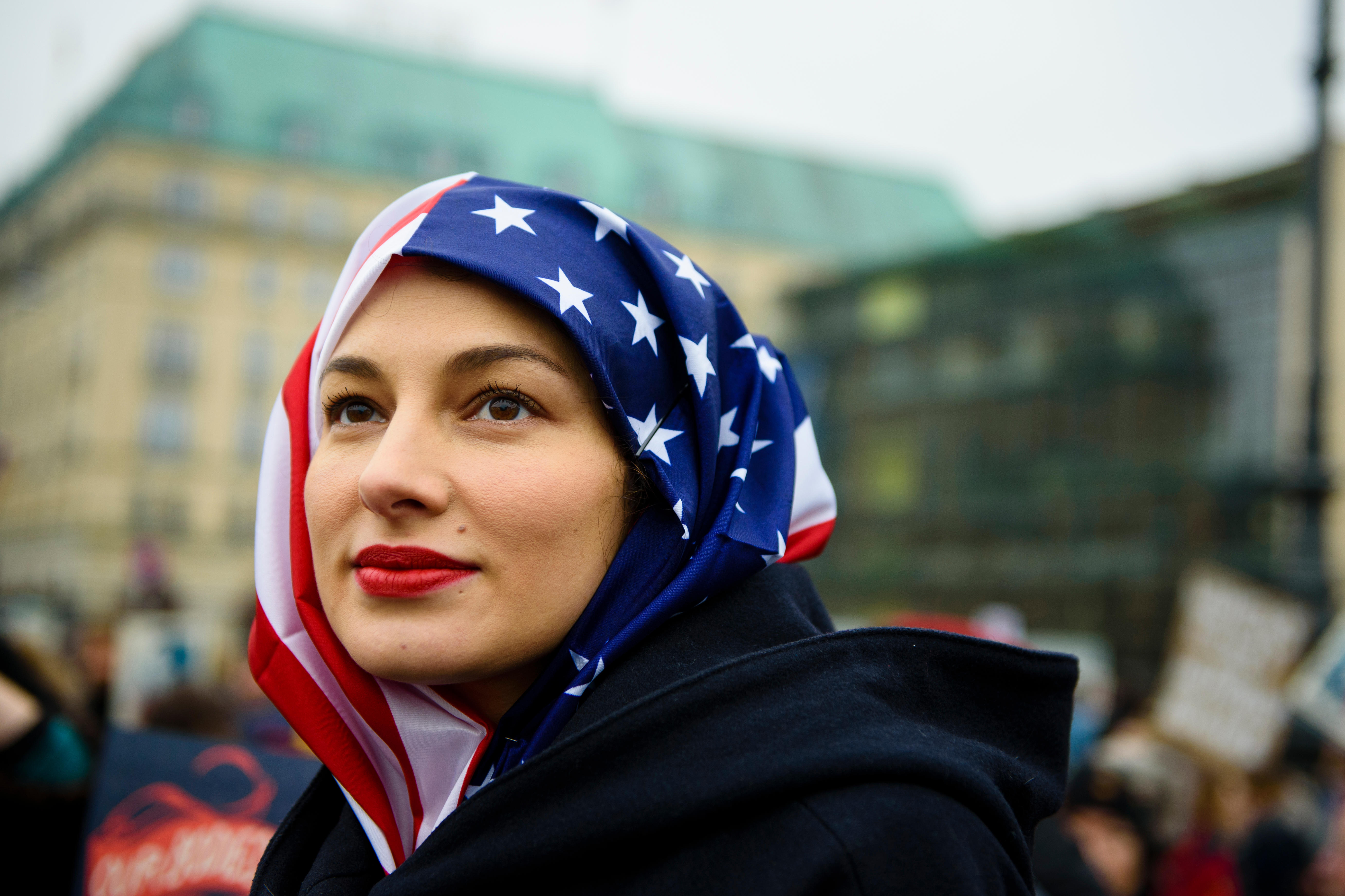 A woman wears a U.S. flag like a hijab during a protest of U.S. Democrats Abroad in front of the Brandenburg Gate in Berlin, on Jan. 21, 2017.