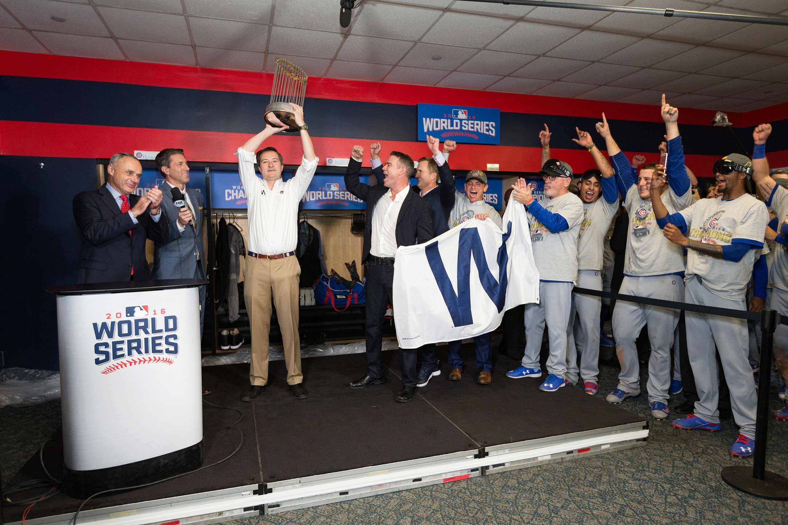 Chicago Cubs owner Tom Ricketts lifts up the World Series trophy after the Cubs win their first championship title since 1908, Nov. 2, 2016.